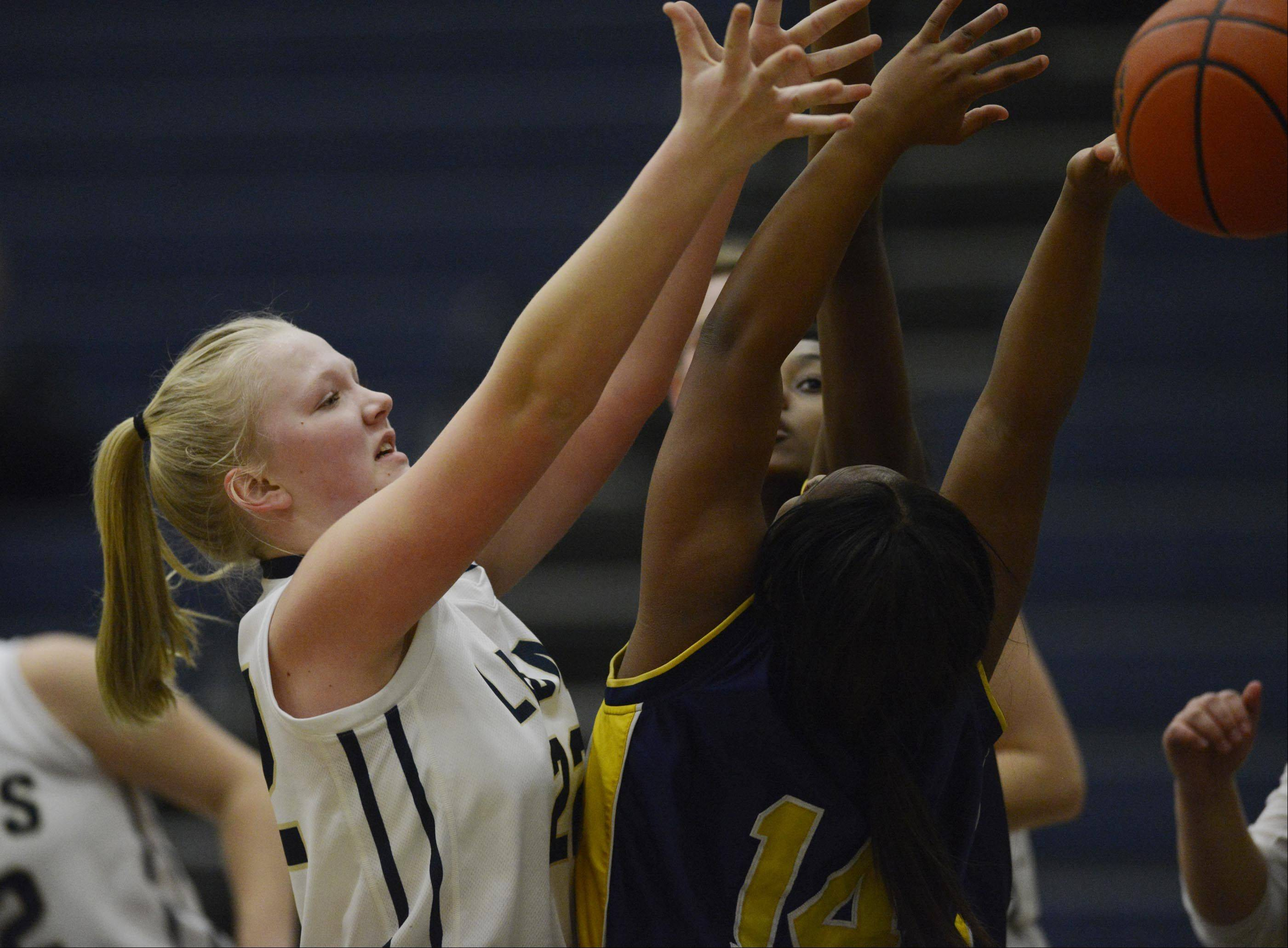 Harvest Christian Academy's Rachel Oostdyk reaches for a rebound against Cristo Rey St. Martin's Jessena Fields Monday in Elgin.