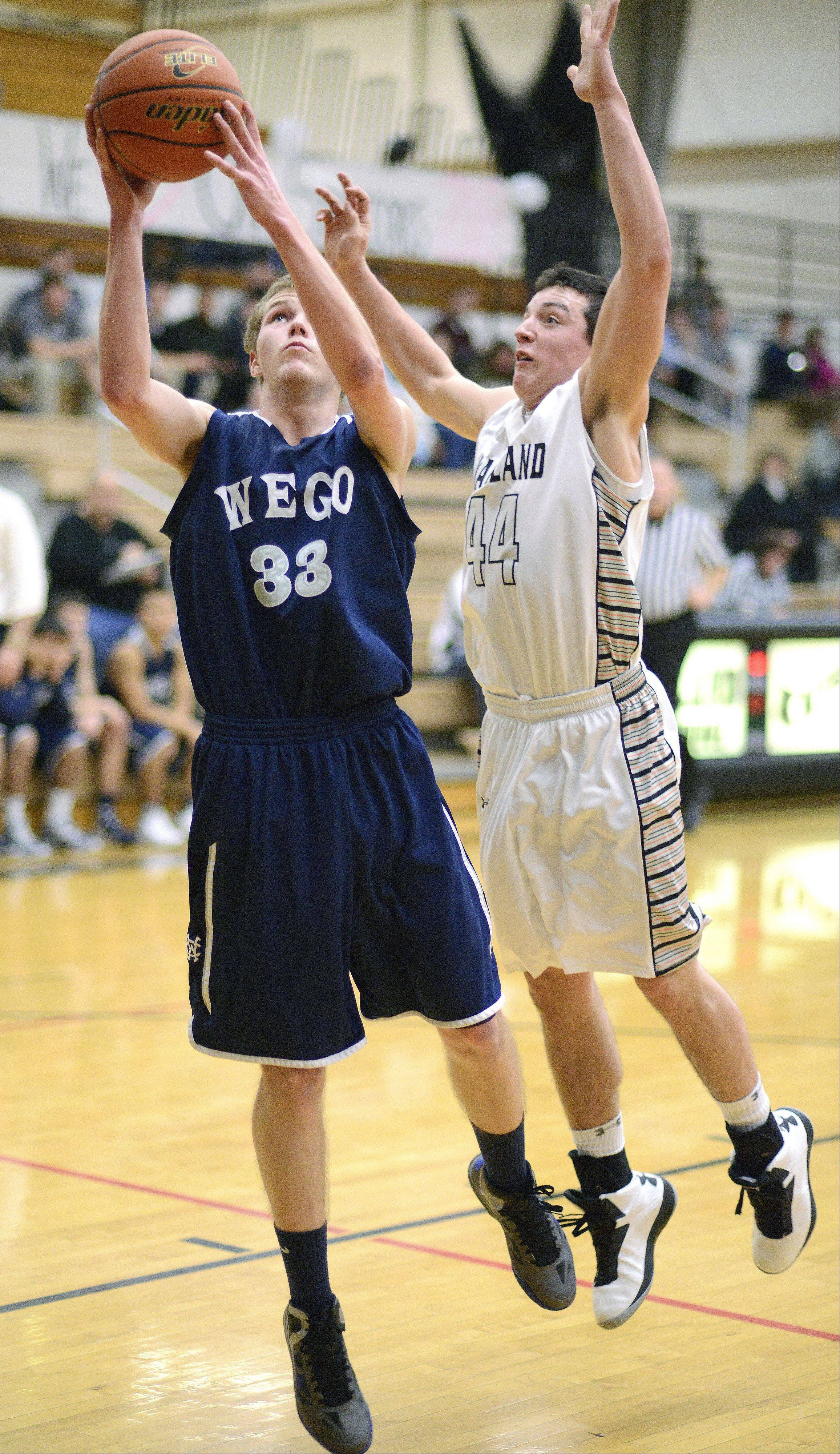 West Chicago's Mike Zajac is fouled by Kaneland's Matt Limbrunner as he makes a shot for the basket in the third quarter on Tuesday, February 5.