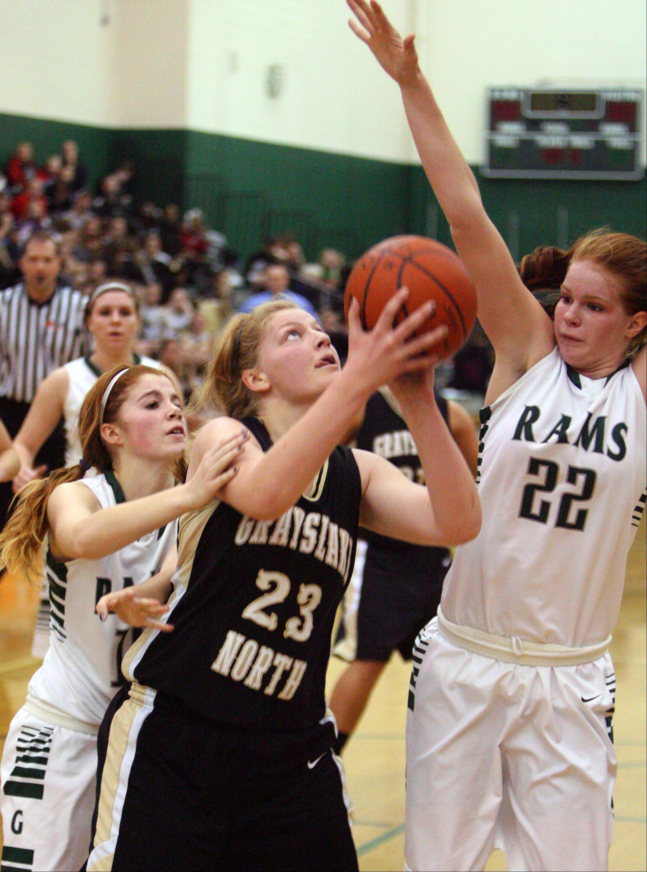 Grayslake North's Joanna Guhl, center, drives past Grayslake Central's Lauren Spaulding, left, and Morgan Dahlstrom on Tuesday night at Grayslake Central.
