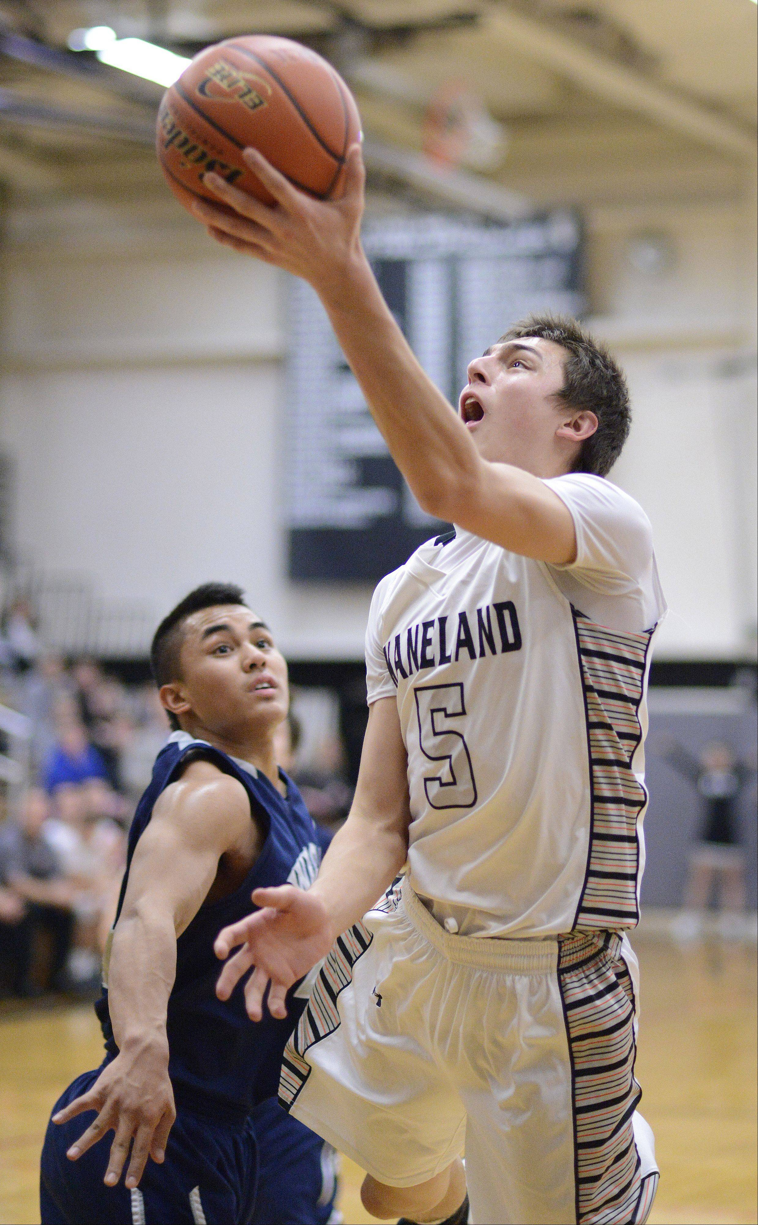 West Chicago's Marco Lomibao tries to block as Kaneland's John Pruett sinks a shot in the first quarter.