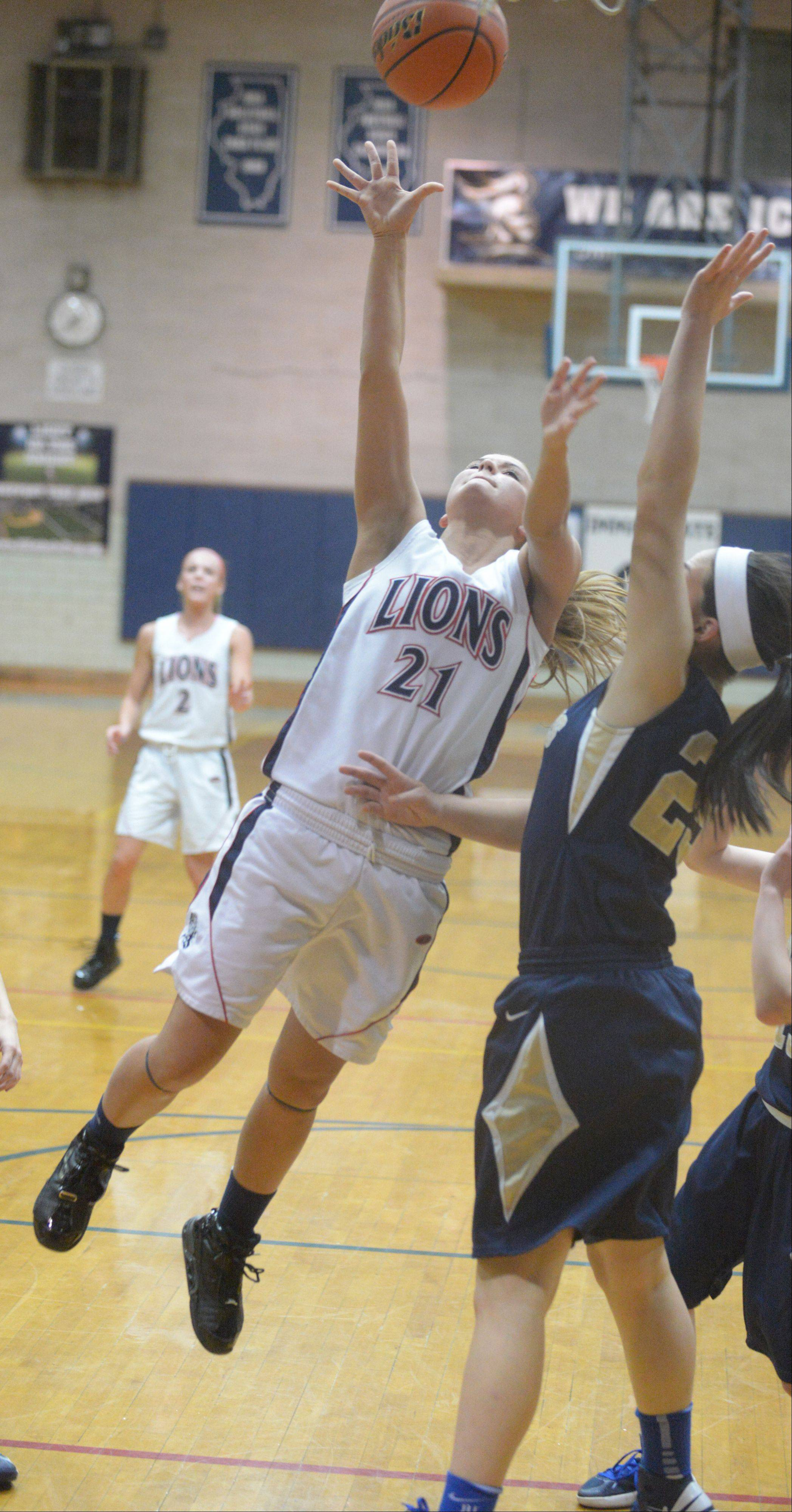 Kelly Urban of Lisle takes one to the net while Anjella Farmer blocks.