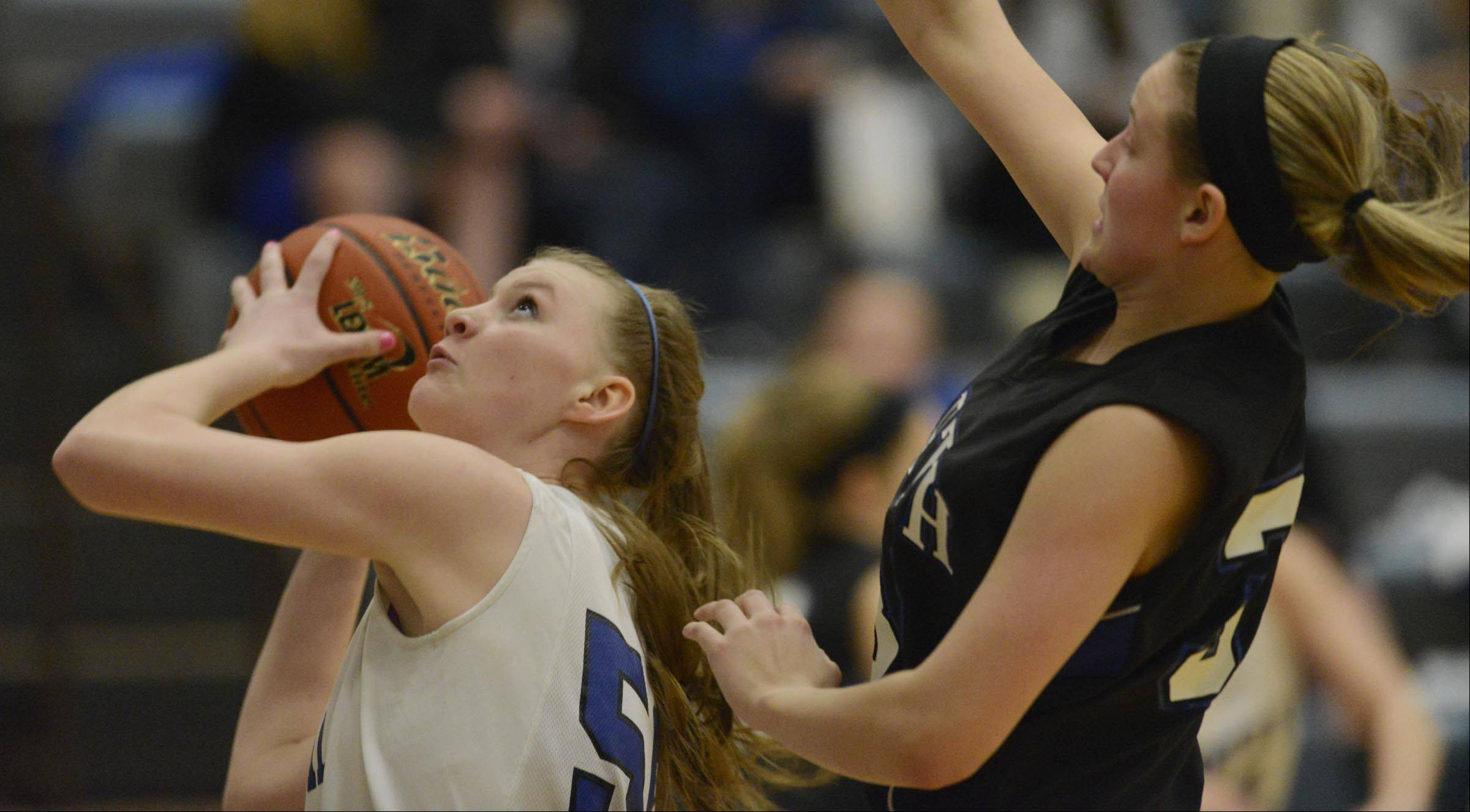 Burlington Central's Rebecca Gerke shoots under the defense of St. Charles North's Nicole Davidson.