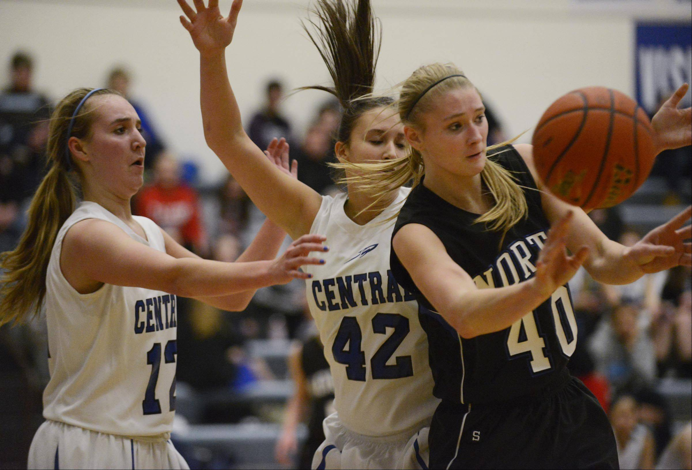 St. Charles North's Morgan Rosencrants passes the ball back out after running into the defense of Burlington Central's Shelby Holt, left, and Alison Colby.