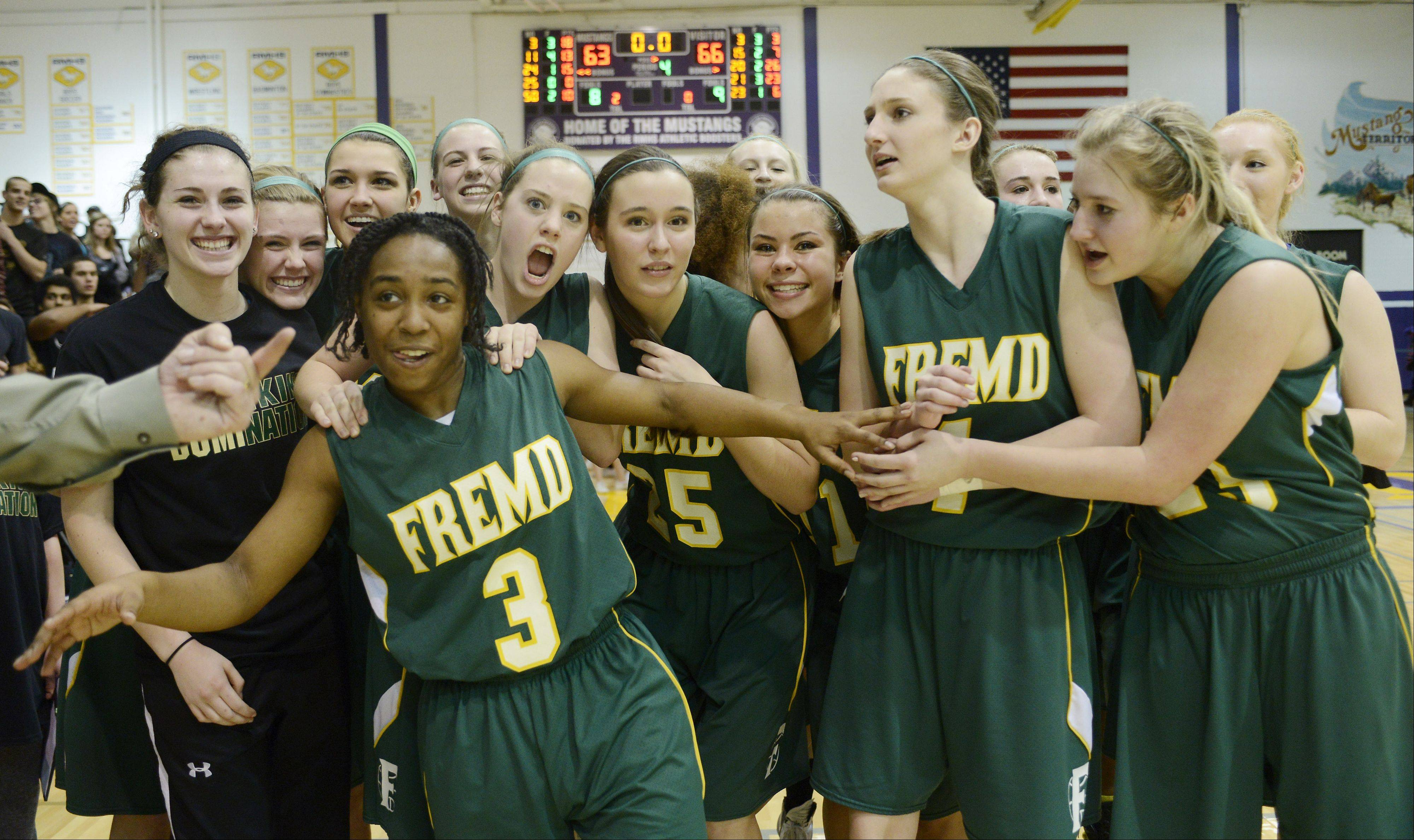 Fremd freshman Brianna Lewis, middle, celebrates with her teammates after hitting the game-winning shot in overtime to beat Rolling Meadows in Wednesday's Mid-Suburban League championship game.