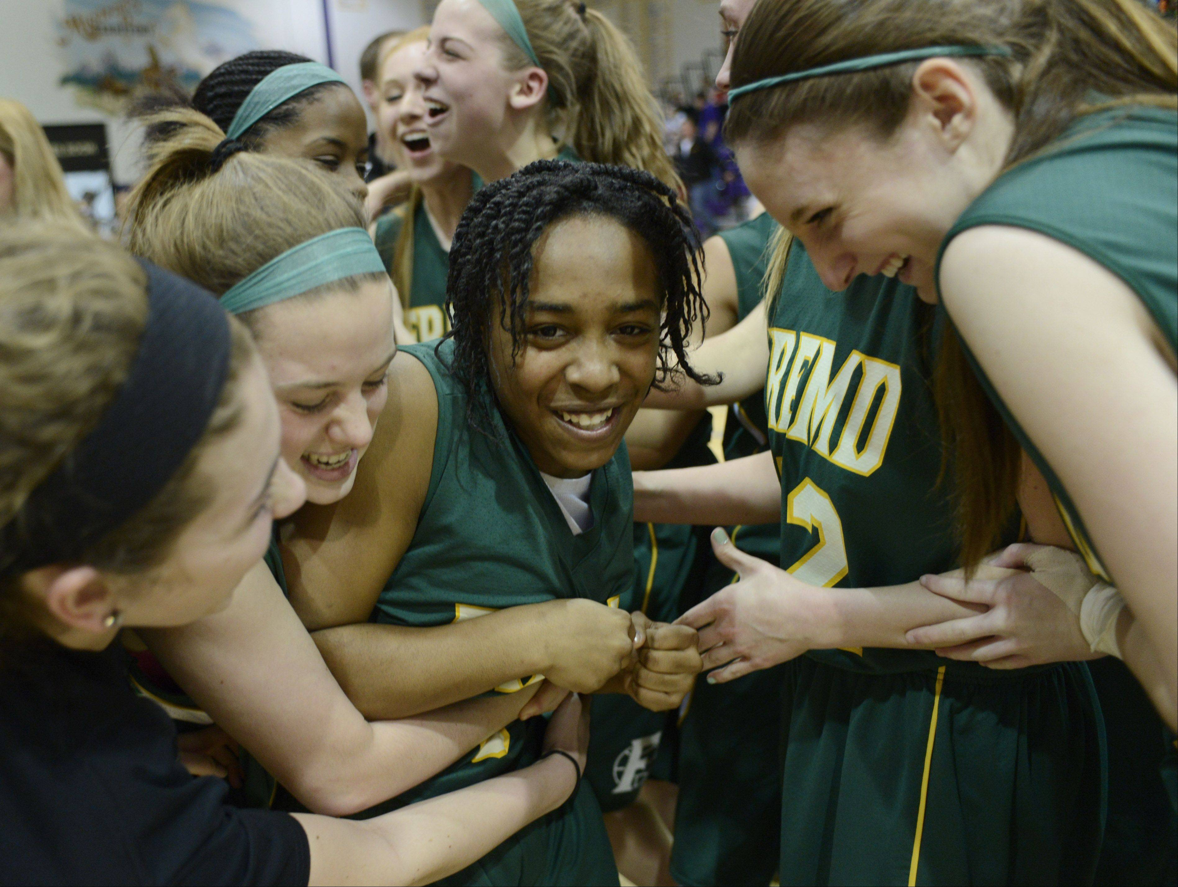 Fremd freshman Brianna Lewis, middle, is mobbed by teammates after she hit the game-winning shot in overtime to beat Rolling Meadows in Wednesday's Mid-Suburban League championship game.