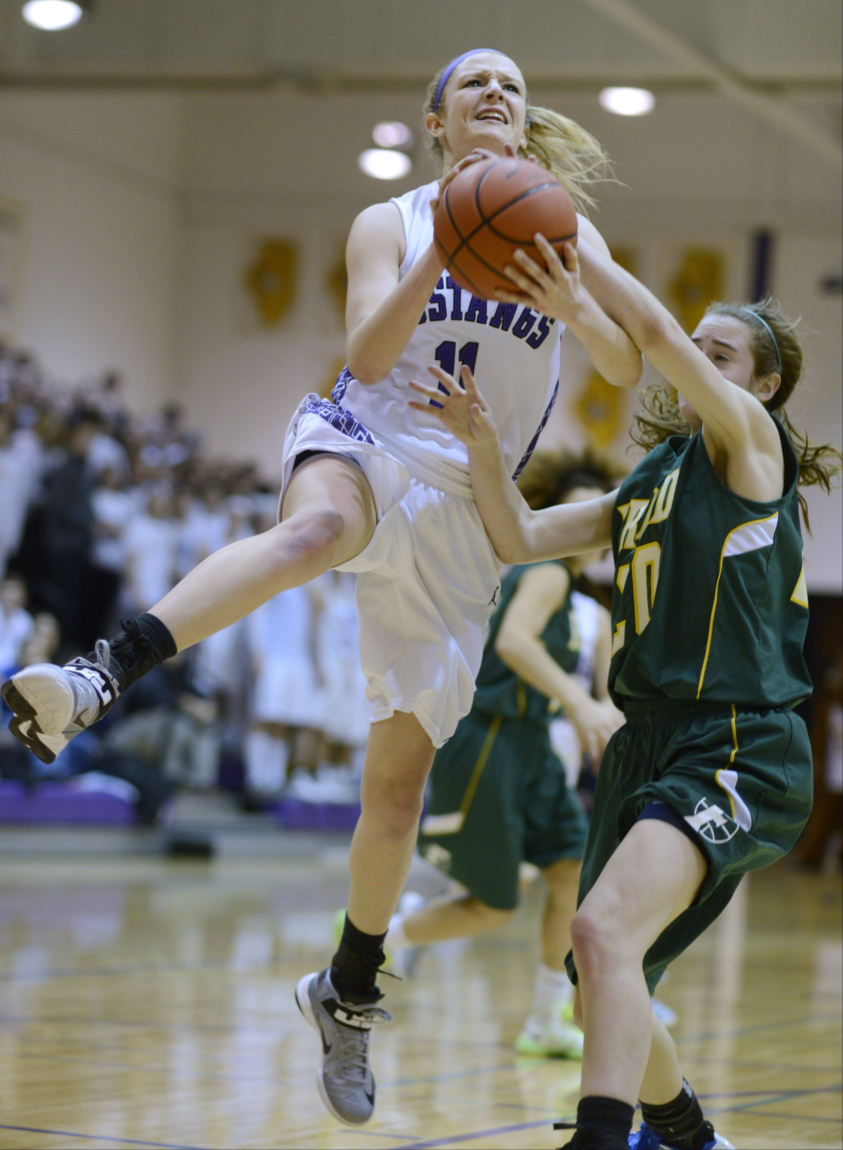 Jenny Vliet of Rolling Meadows draws contact from Fremd's Haley Gorecki as she nears the basket during the Mid-Suburban League championship game Wednesday.