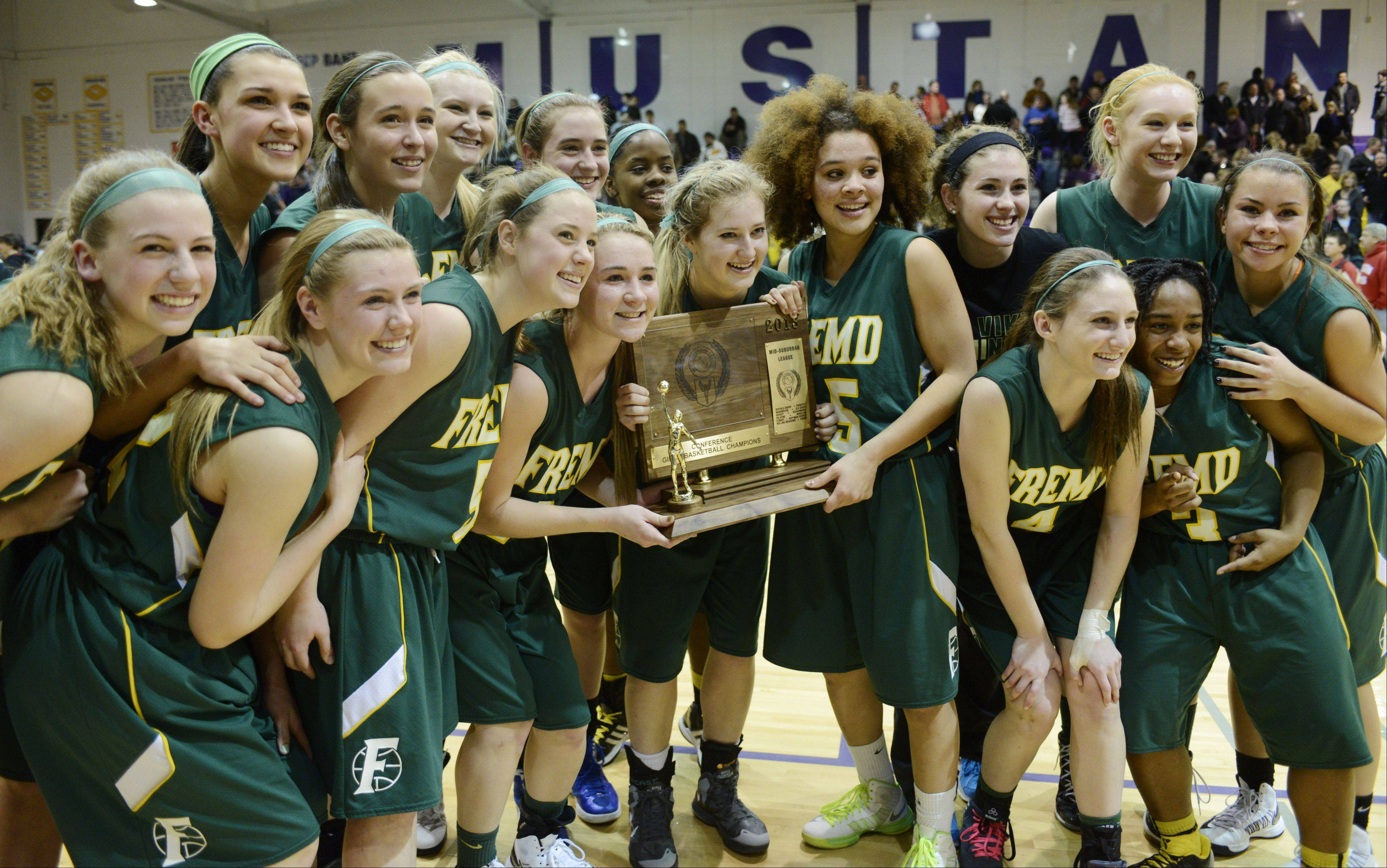 Members of the Fremd girls basketball team pose with their trophy after defeating Rolling Meadows in overtime during the Mid-Suburban League championship game Wednesday.