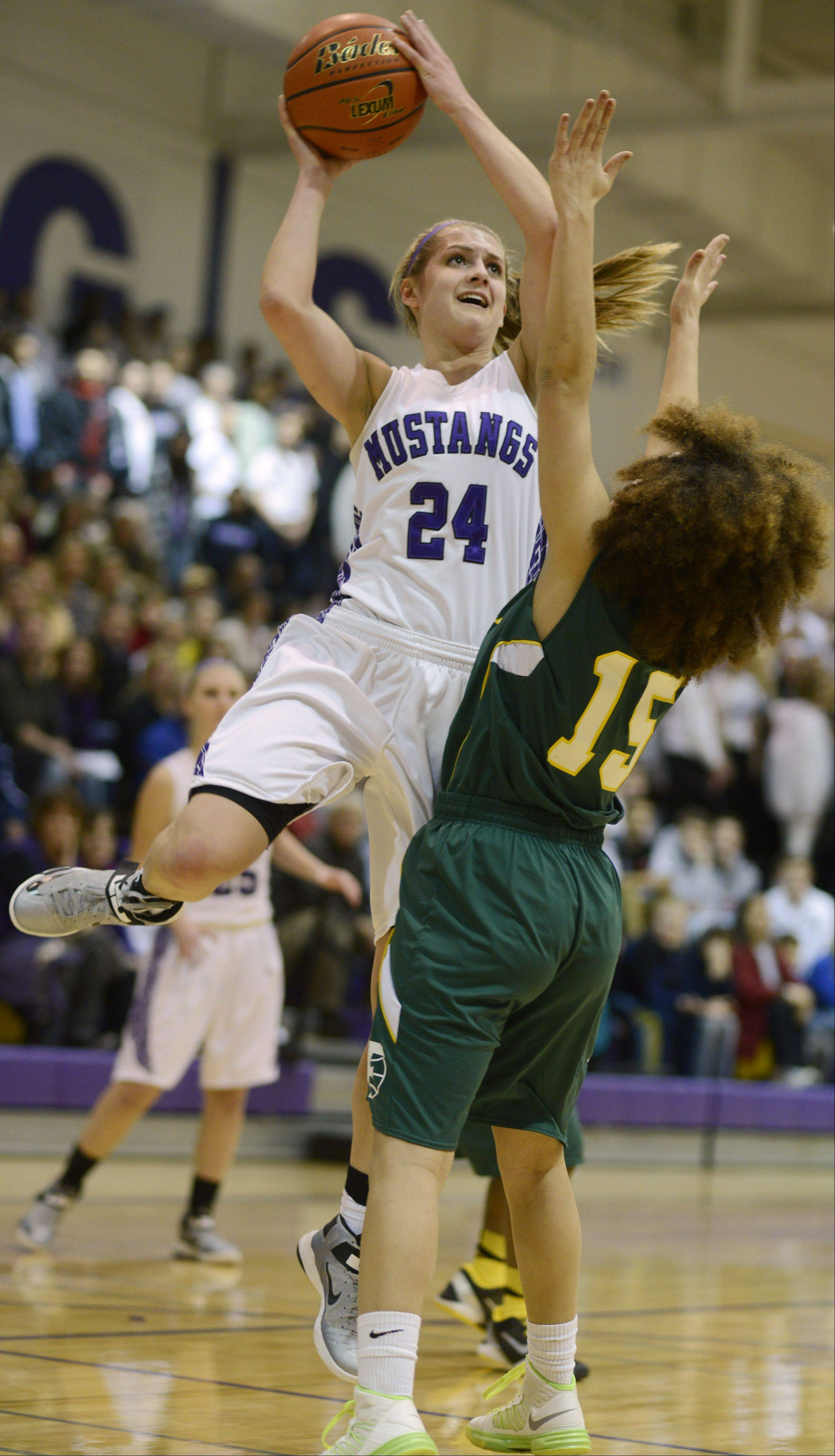 Rolling Meadows' Alexis Glasgow, left, takes a shot in front of Fremd defender Bernie Williams during the Mid-Suburban league championship game Wednesday.