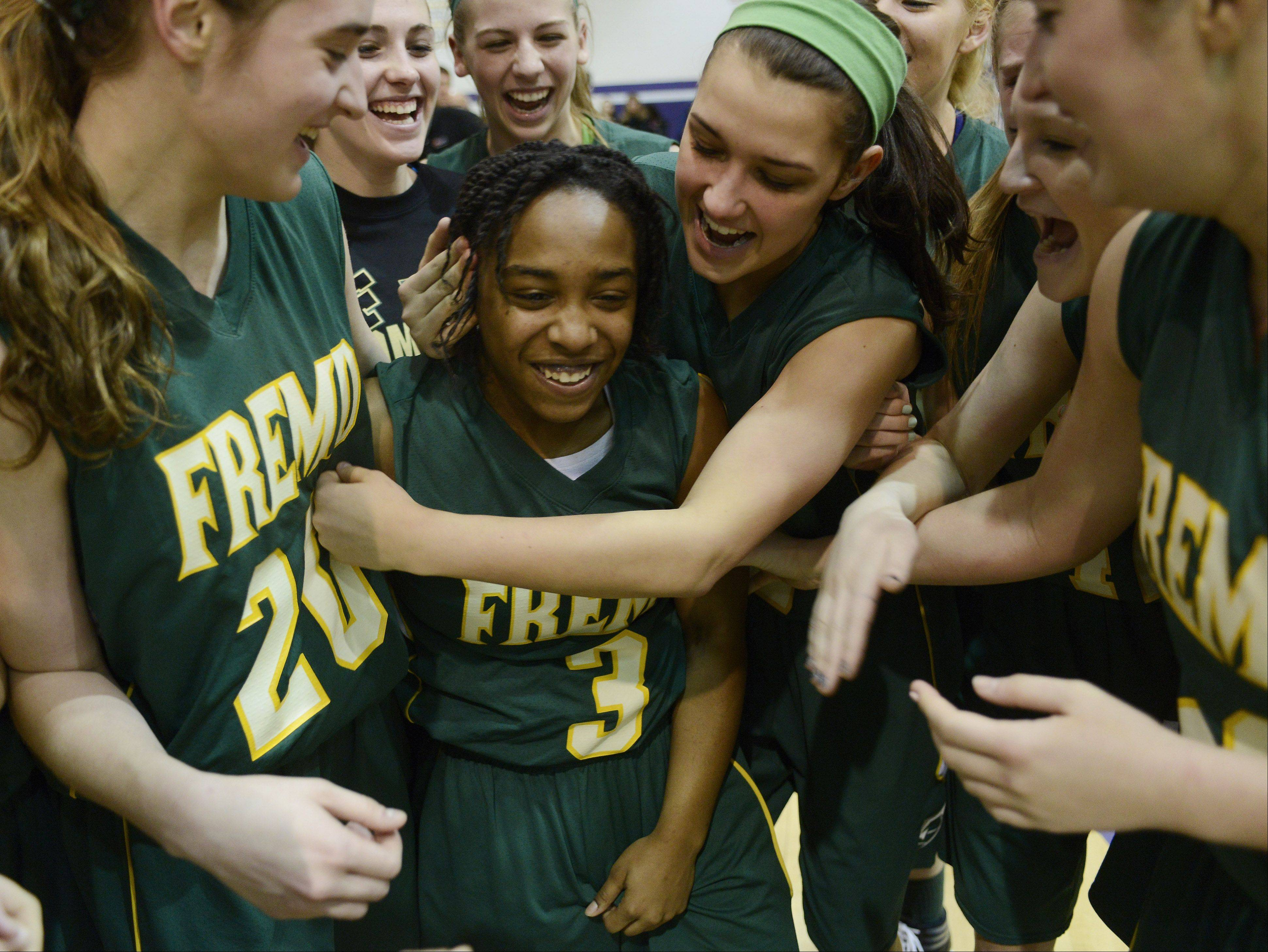 Fremd freshman Brianna Lewis, middle, is mobbed by teammates after hitting the game-winning shot in overtime to beat Rolling Meadows in Wednesday's Mid-Suburban League championship game.