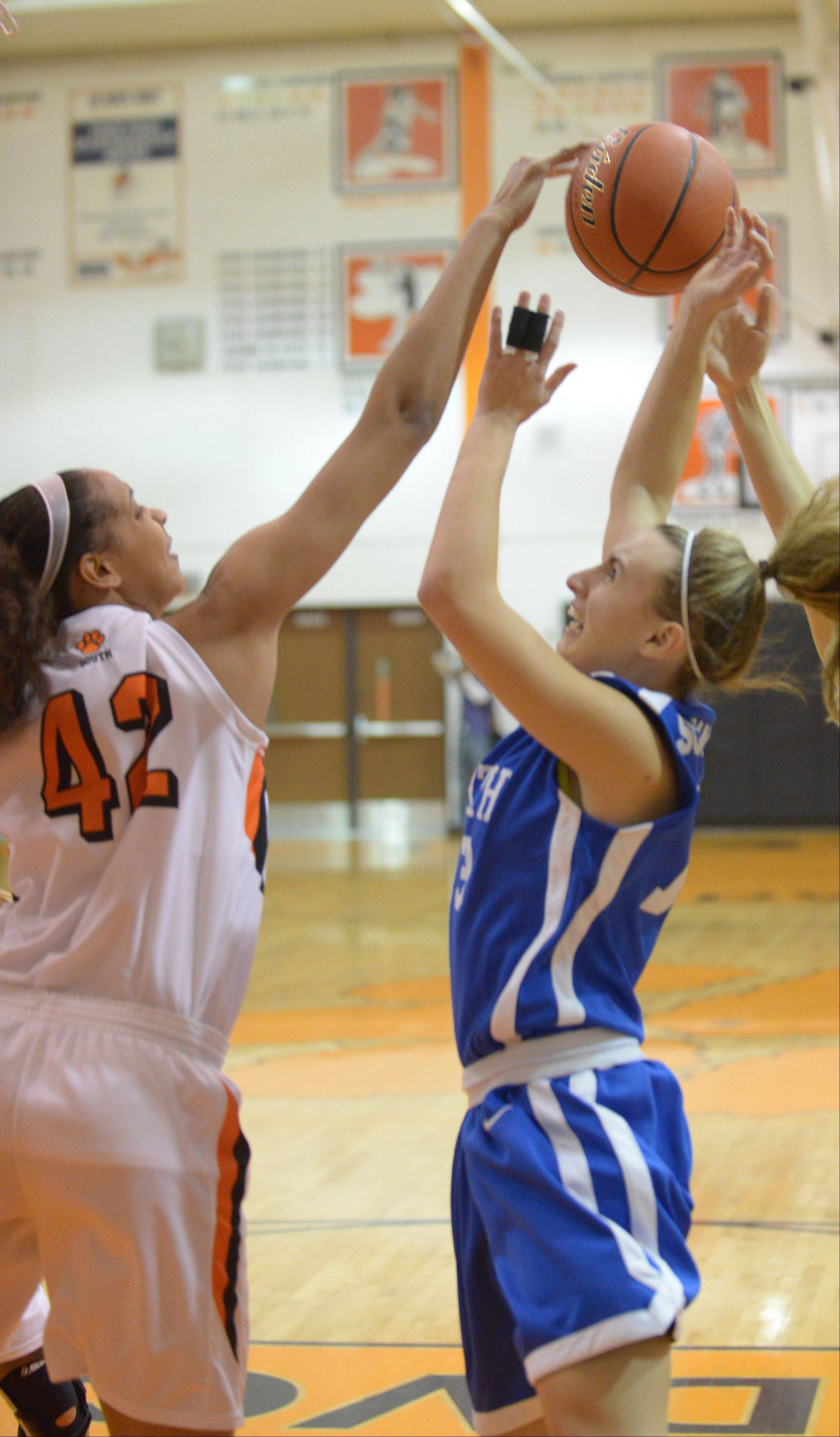 Diamond Thompson of Wheaton South,left, tries to block Brooke Schanowski of Wheaton North during the Wheaton North at Wheaton Warrenville South girls basketball game Thursday.
