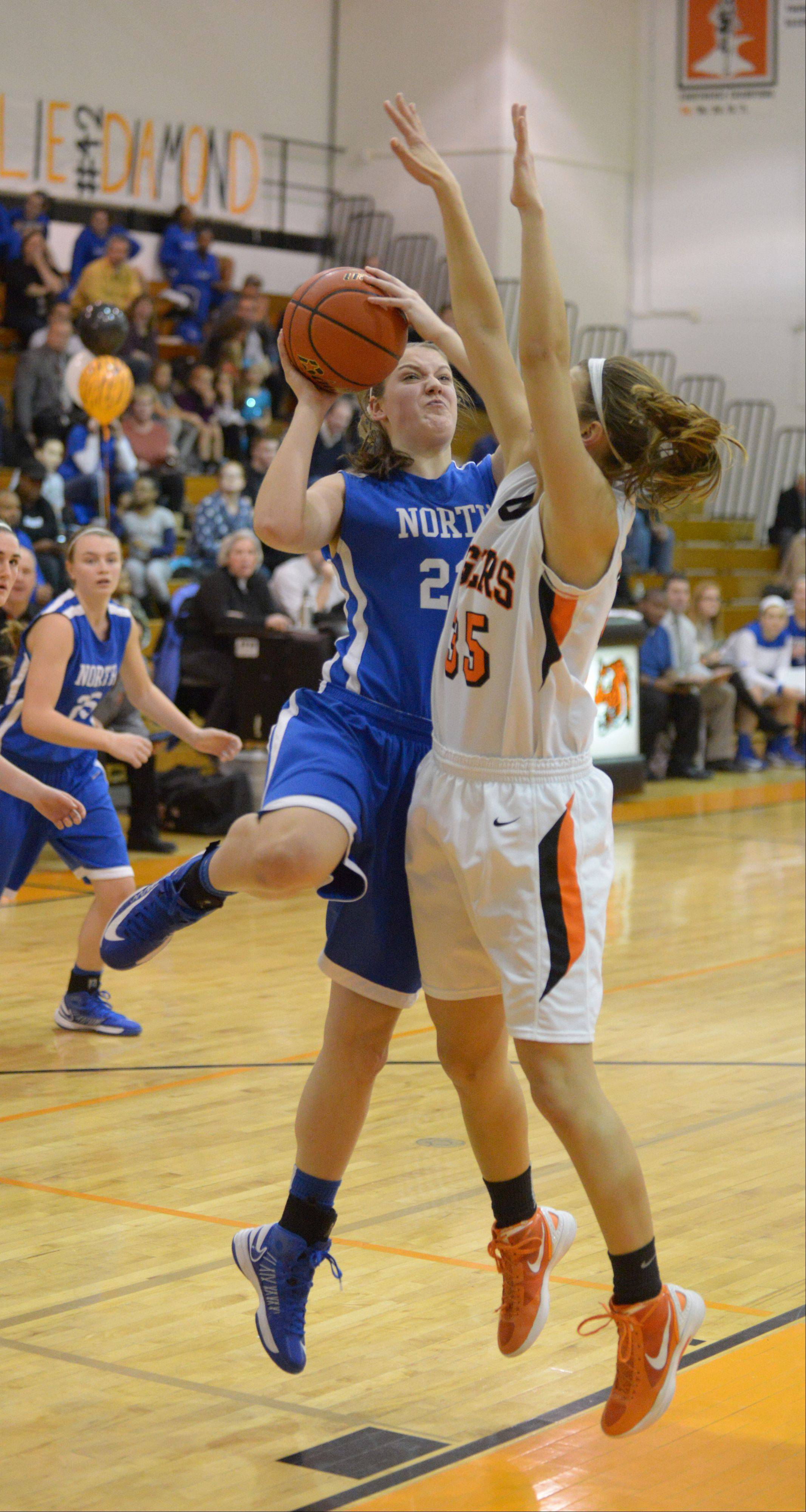 Chrissy Baird of Wheaton North takes a shot over Allie Zappia of Wheaton Warrenville South.