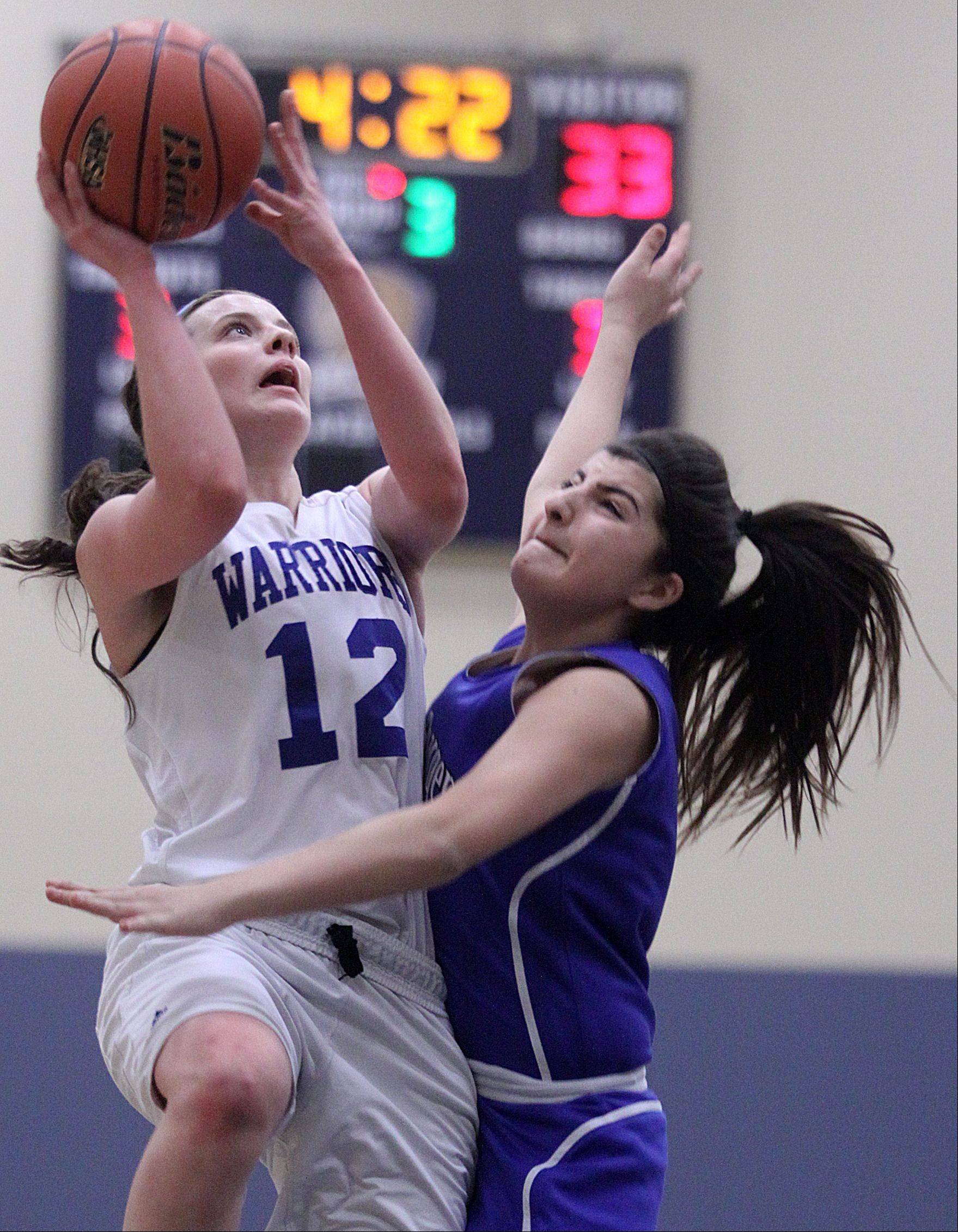 Westminster Christian's Maddie Versluys, left, takes the ball to the hoop against Christian Liberty Academy's Samantha Amedin during the Class 1A Harvest Christian regional championship game Friday night.