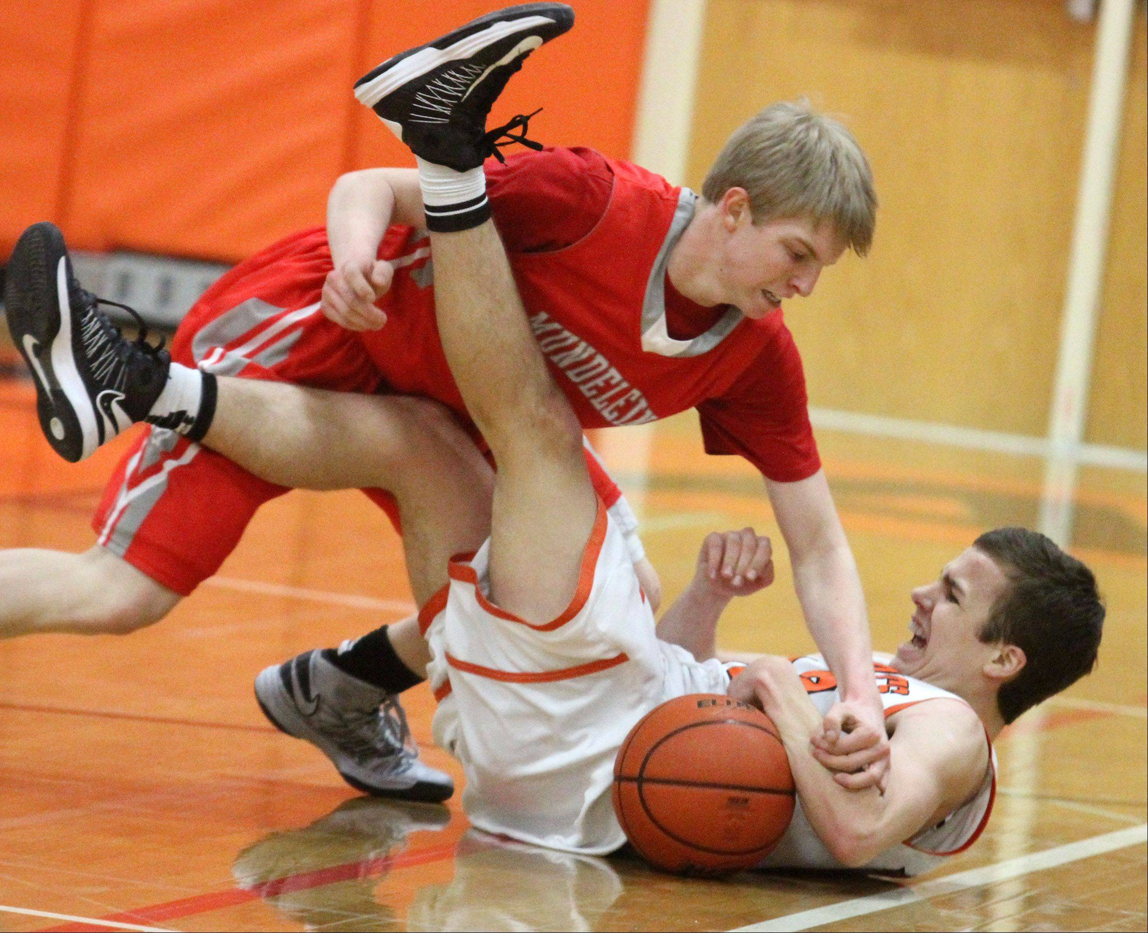 Mundelein defender Dylan Delaquila tries to take the ball from Libertyville guard Nick Carlucci after the two collided in the first half at Libertyville on Friday.
