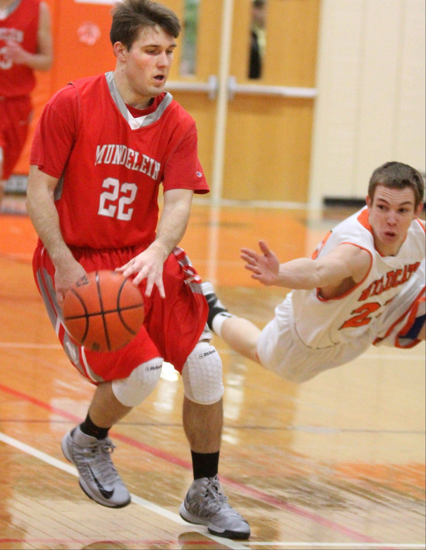 Mundelein guard Robert Knar pushes the ball past mid court as Libertyville defender Bryan Scanlan dives for the ball at Libertyville on Friday, February 8, 2013.