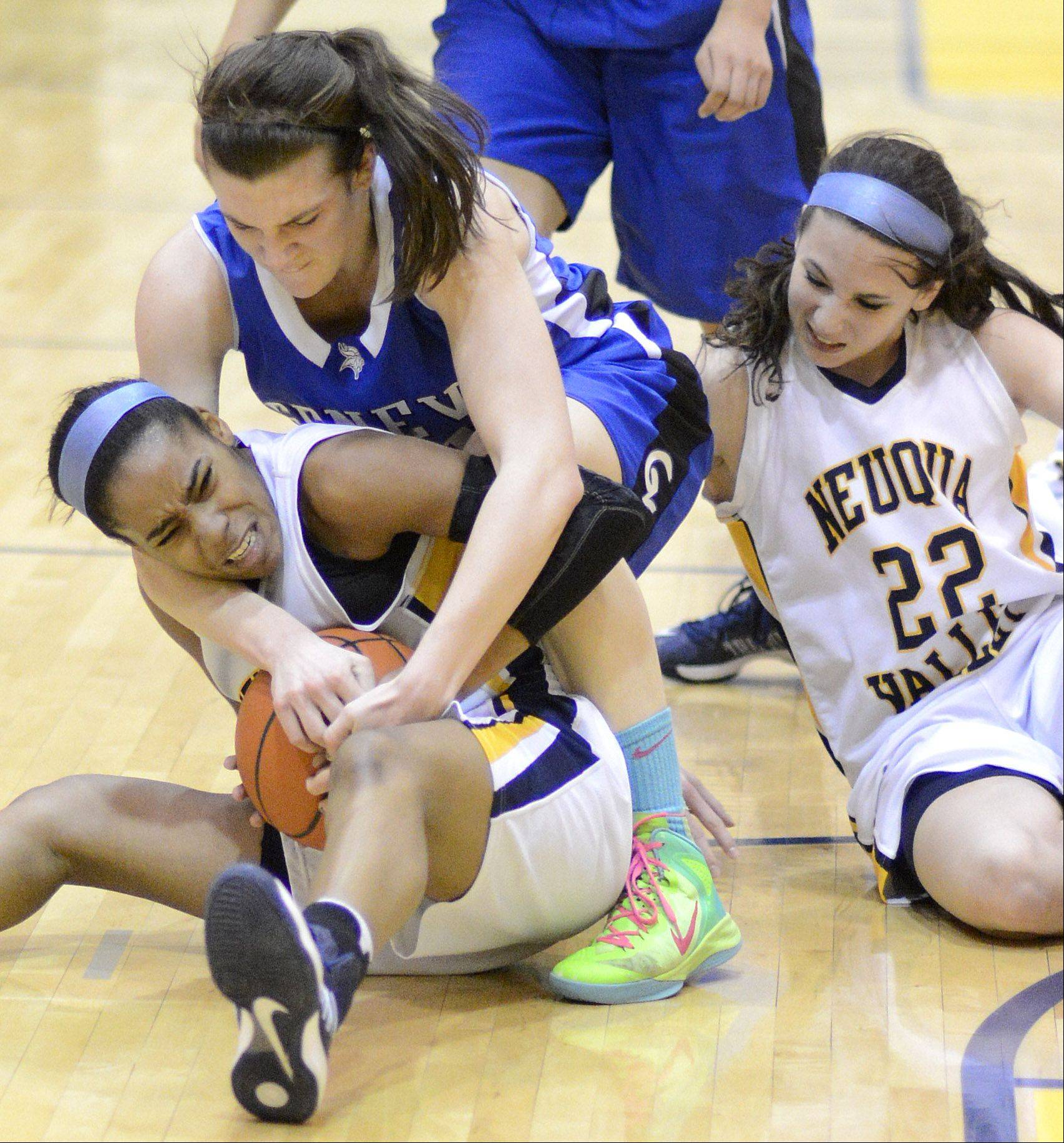 Neuqua Valley's Malia Smith holds on tight to a loose ball while she and teammate Bryce Menendez fight off Geneva's Sami Pawlak in the quarter of Upstate Eight championship on Friday, February 8.
