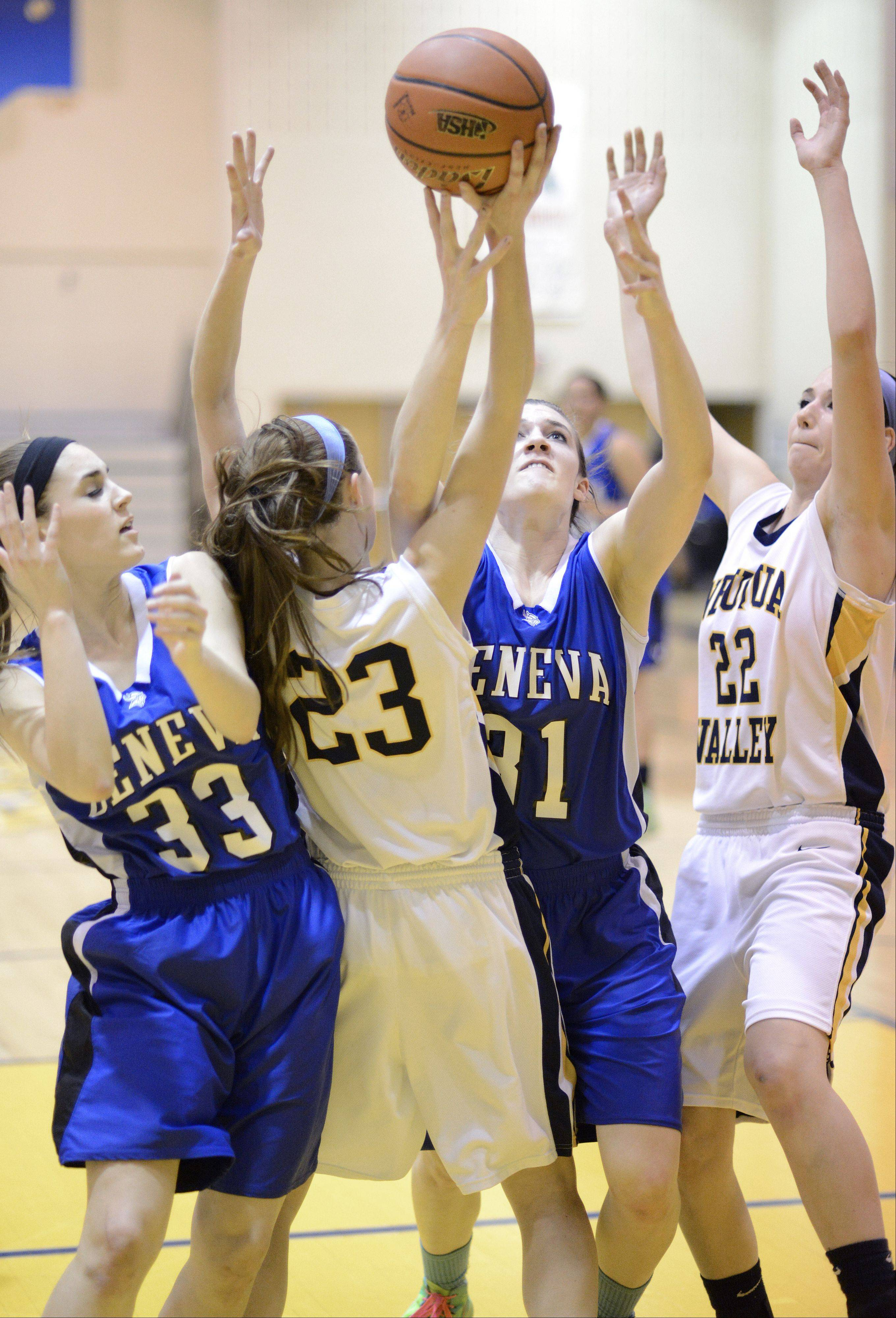 Neuqua Valley's Allison Hedrick (23) and Bryce Menendez (22) leap for a rebound with Geneva's Madeline Dunn (33) and Sami Pawlak (31) in the second quarter of the Upstate Eight championship on Friday, February 8.
