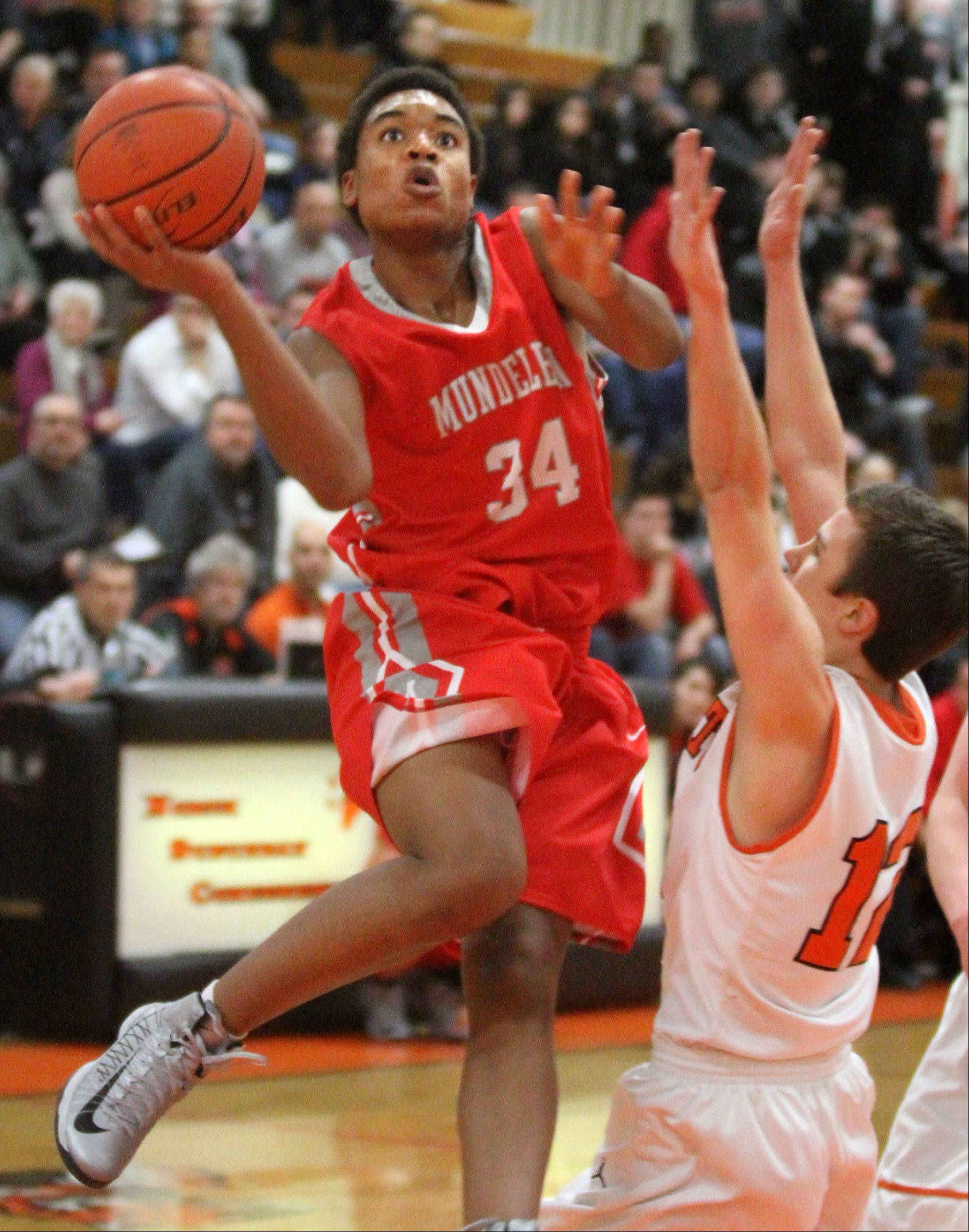 Mundelein's Cliff Dunigan shoots around Libertyville defender Nick Carlucci.