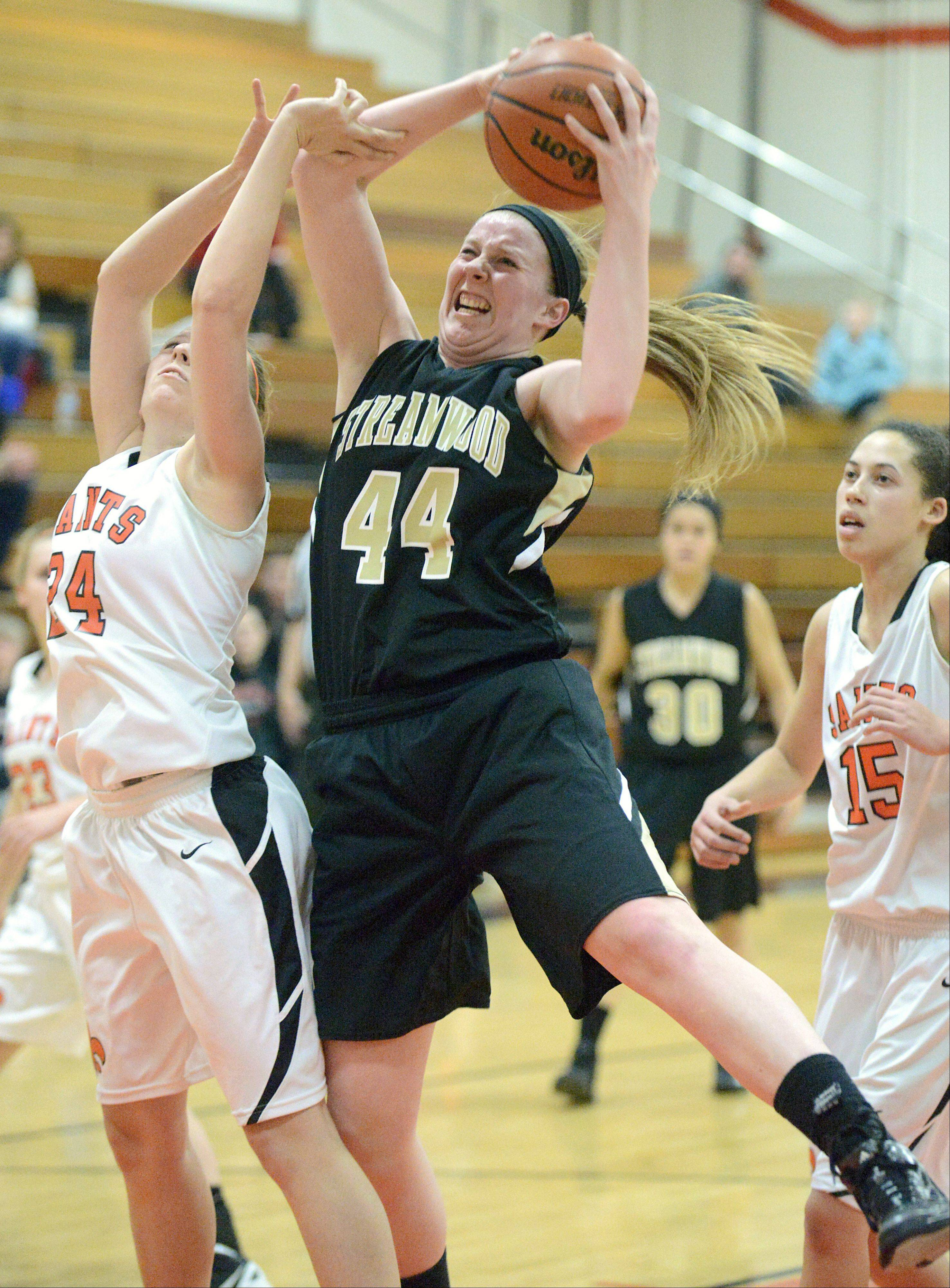 Streamwood's Hannah McGlone (44) reaches for a rebound against St. Charles East.