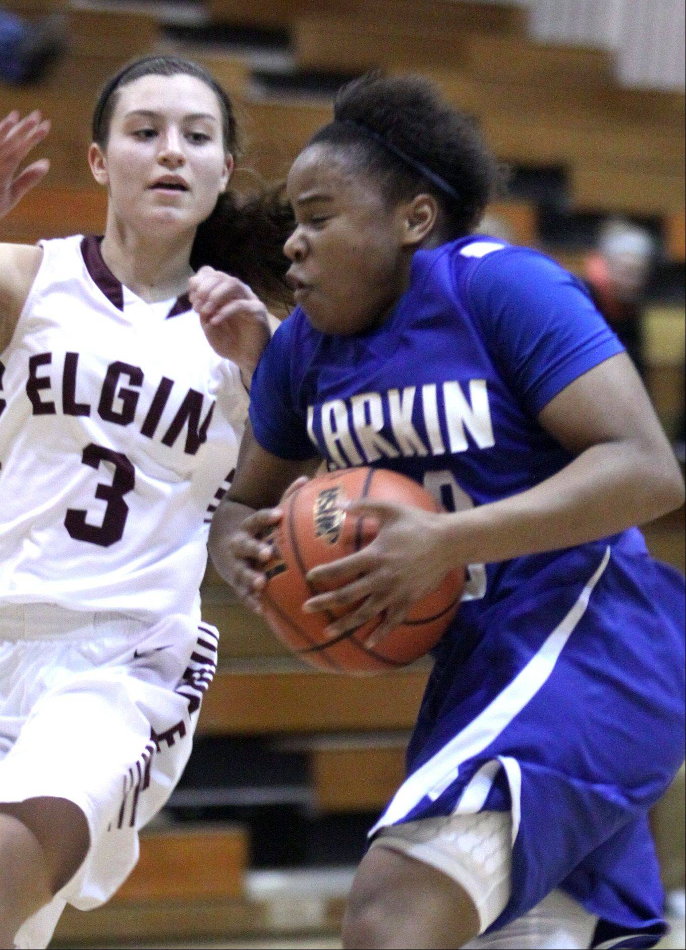 Larkin's Quixmia Washington, right, takes the ball to the hoop past Elgin's Maggie Powers during a regional game at Streamwood High School on Monday night.