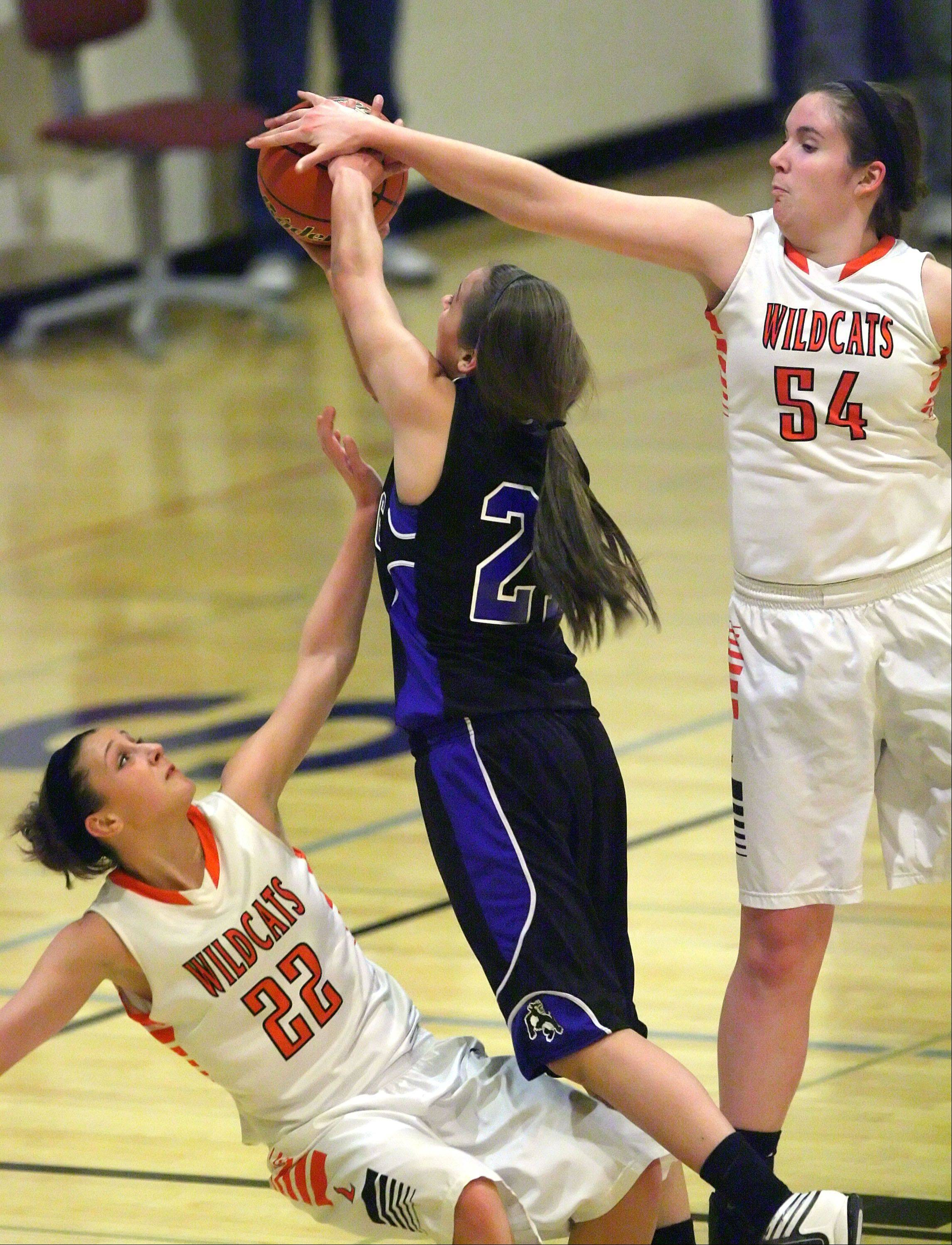 Wheeling's Deanna Kuzmanic drives in between Libertyville's Olivia Mayer, left, and Becky Deichl during the Class 4A girls basketball regional play-in game Monday night at Wheeling.