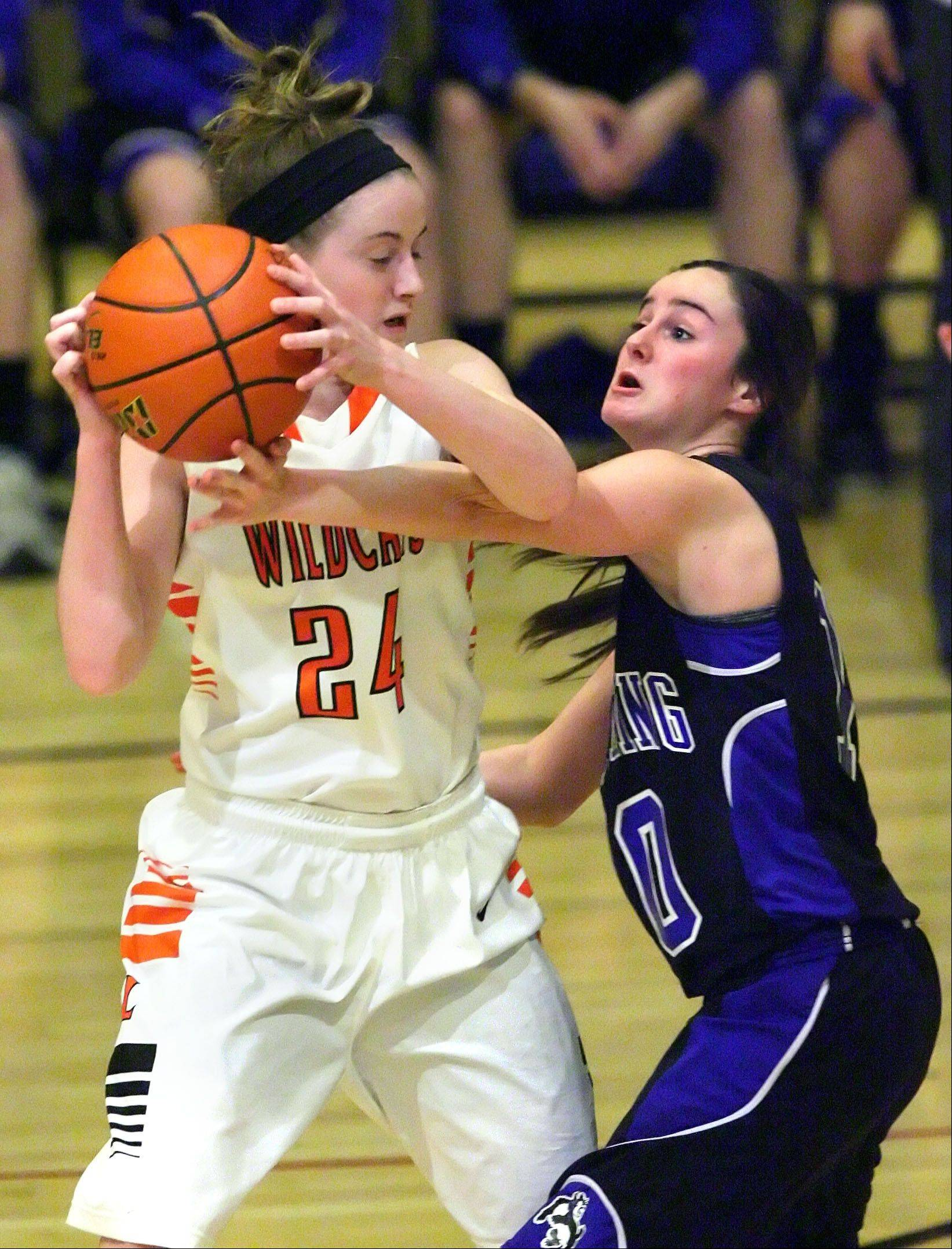 Libertyville's Rosie Lynch and Wheeling's Gianna Calistro battle for the ball during the Class 4A girls basketball regional play-in game Monday night at Wheeling.