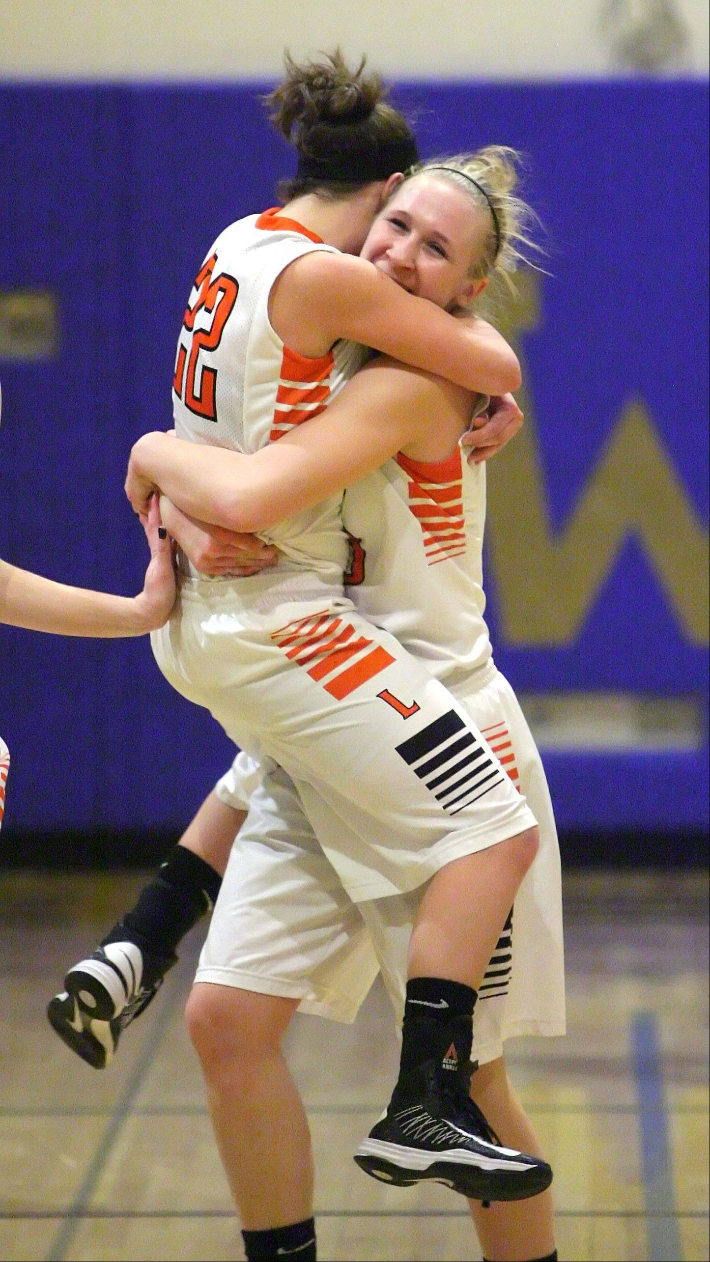 Libertyville's Olivia Mayer, left, jumps into the arms Dana Kym after beating Wheeling in a Class 4A regional play-in game Monday night at Wheeling.