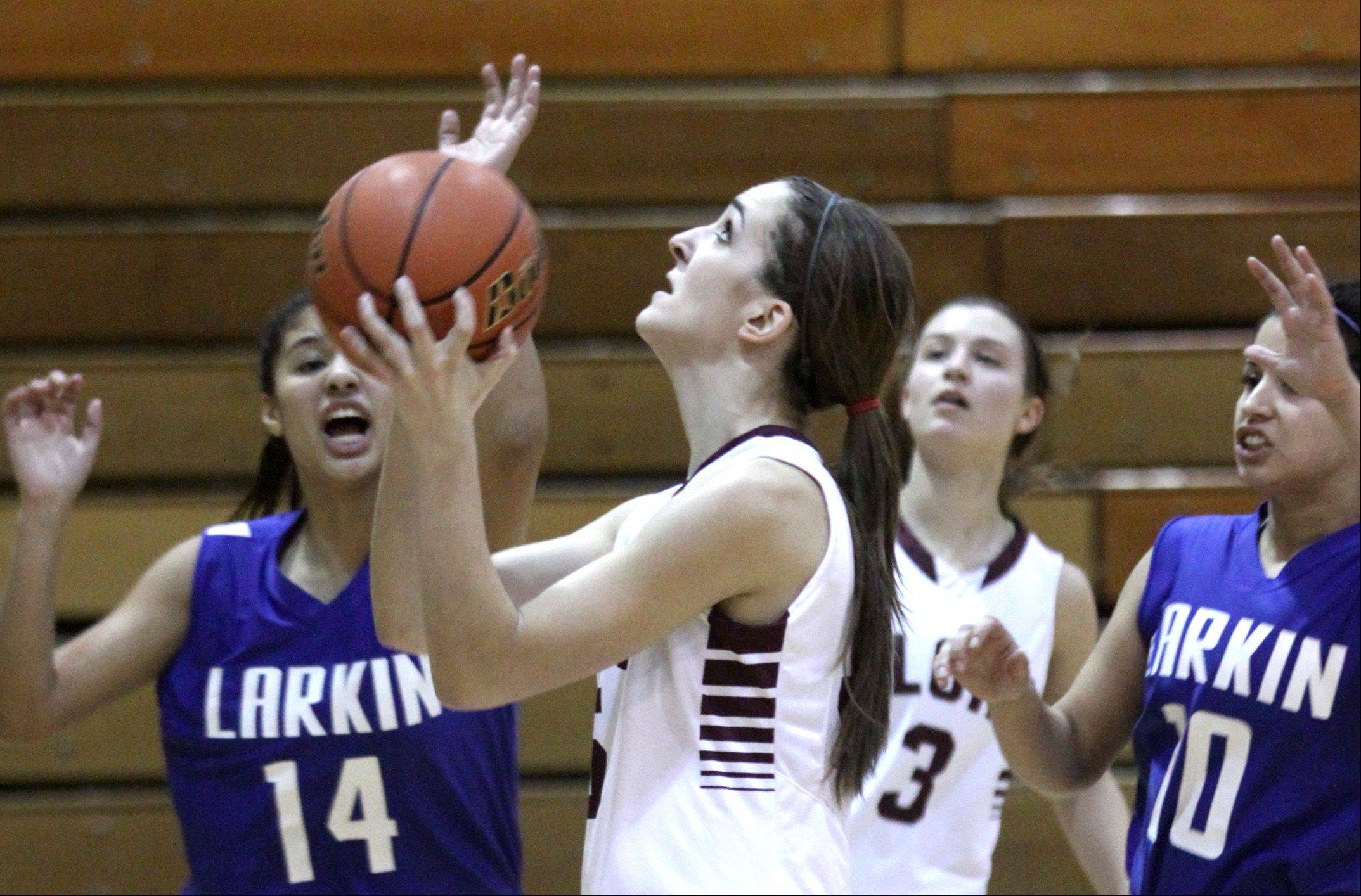 Elgin's Tamara Milosevic, center, takes a shot against Larkin.