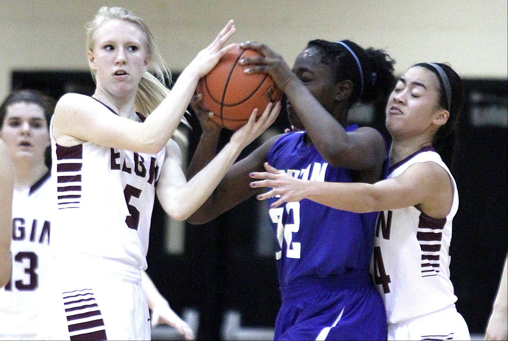 Elgin's Melanie Berg, left, and Kristin Tayag, right, tussle with Larkin's Elizabeth Oladokun, center, for control of the ball.
