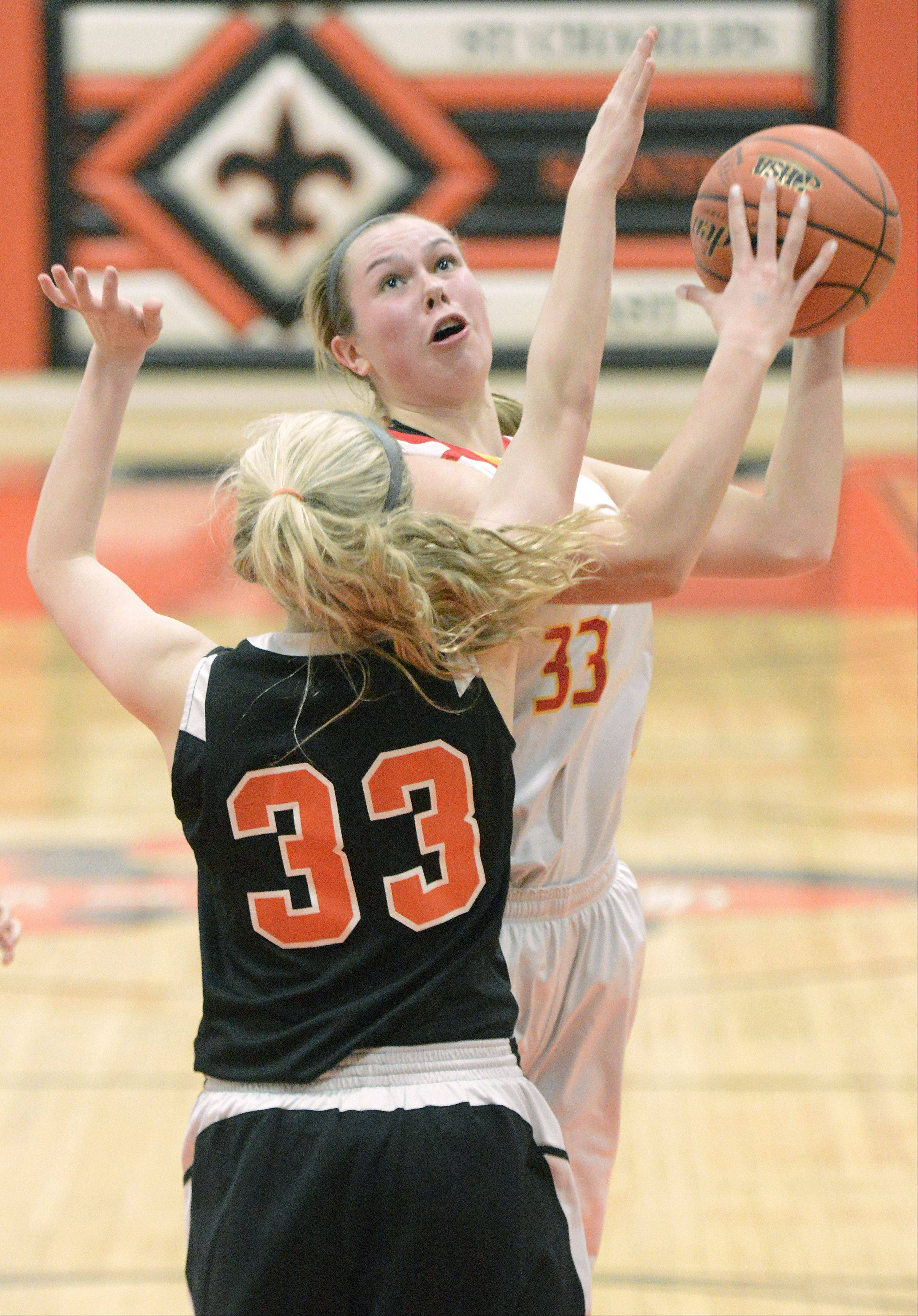 Laura Stoecker/lstoecker@dailyherald.com St. Charles East's Hannah Nowling attempts to block a shot by Batavia's Erin Bayram in the third quarter of the 4A regional on Tuesday, February 12.