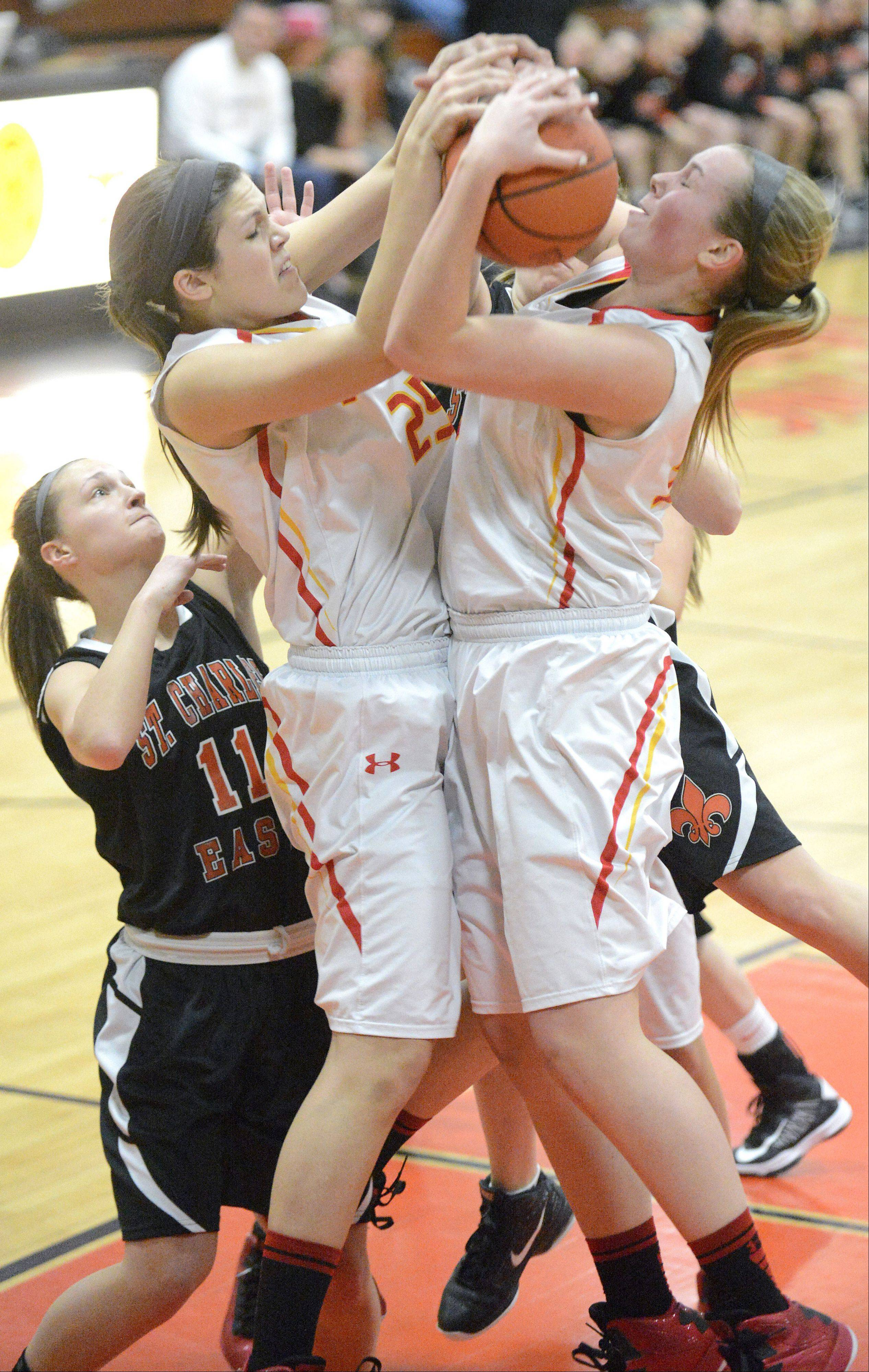 Laura Stoecker/lstoecker@dailyherald.com Batavia's Hannah Frazier and Erin Bayram both grab for a rebound in the third quarter of the 4A regional vs. St. Charles East on Tuesday, February 12.