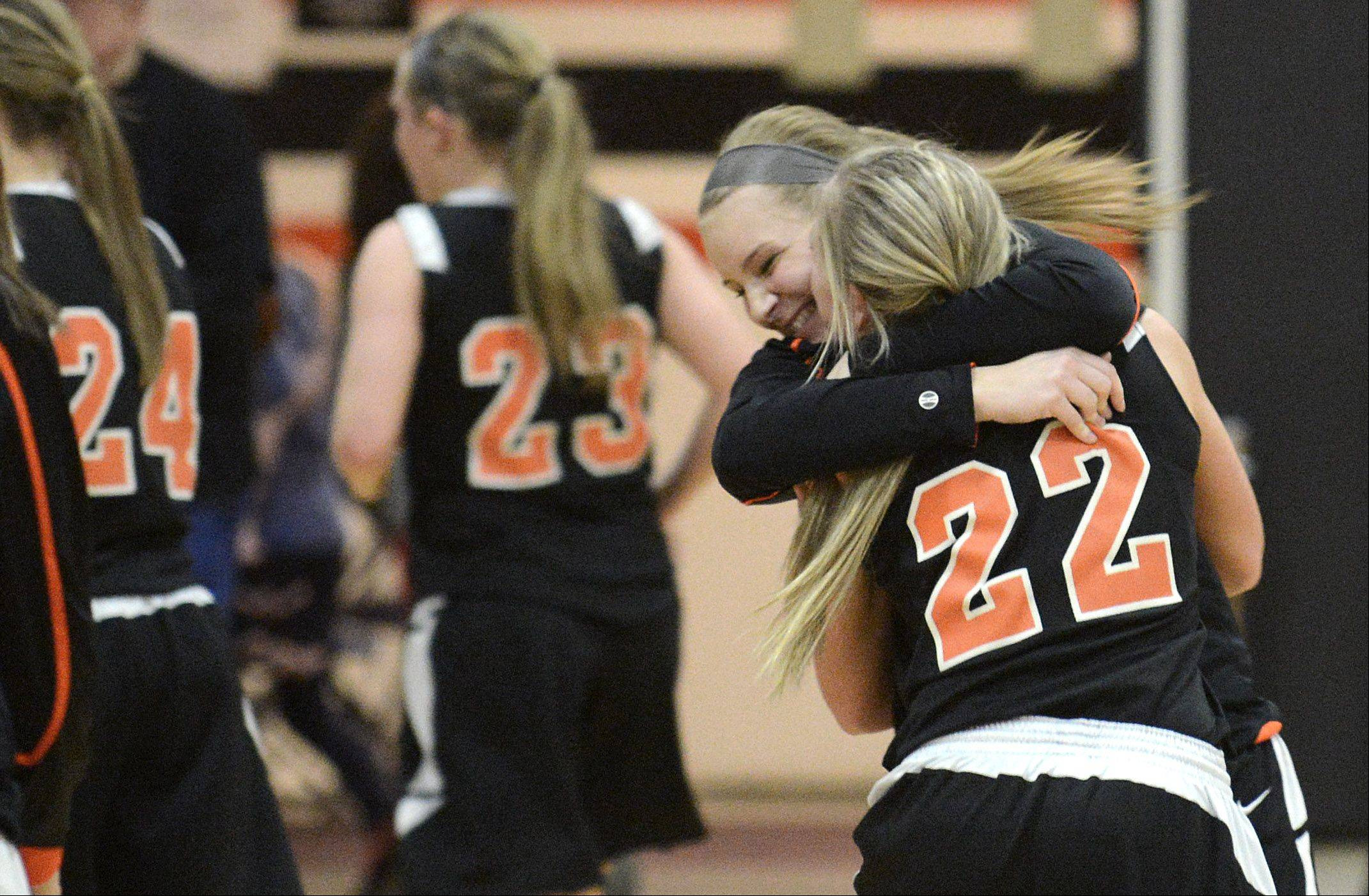 Laura Stoecker/lstoecker@dailyherald.comSt. Charles East's Marlena Detzel (facing) embraces teammate Anna Bartels after their win over Batavia in the 4A regional on Tuesday, February 12.