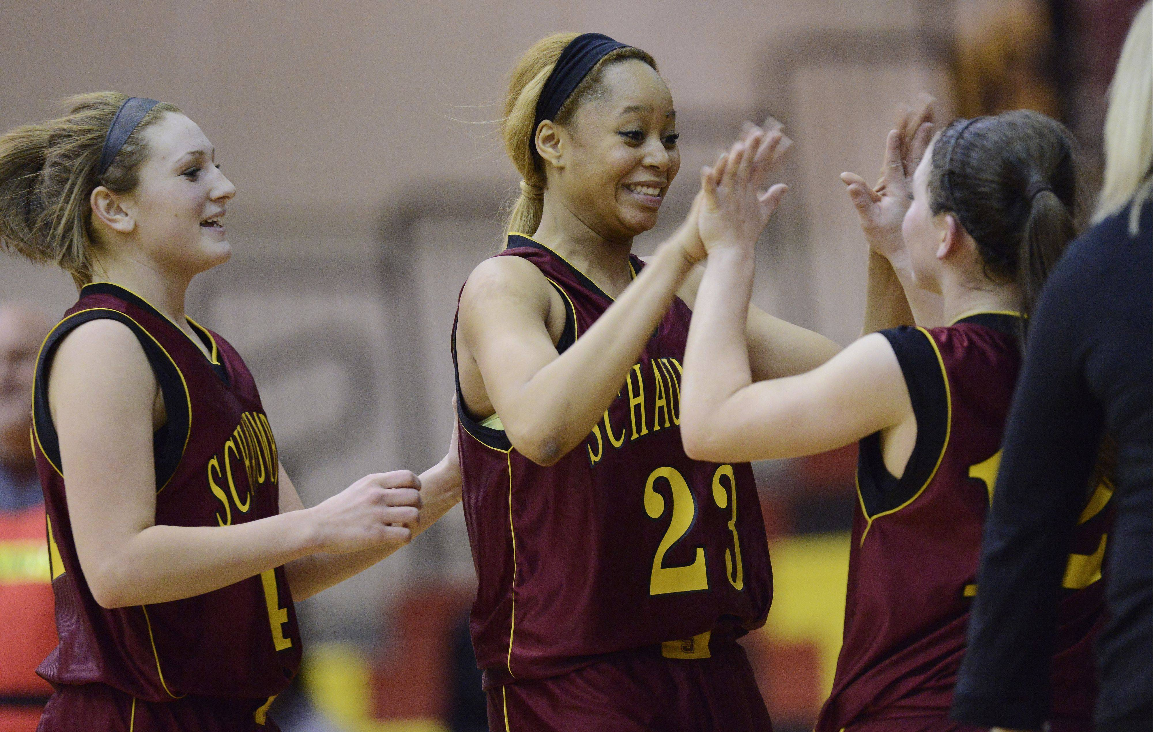 Schaumburg's Jada Blackwell, middle, and Brittany Reinhart, left, celebrate with Amanda Kelly following the Saxons' overtime victory in Class 4A regional semifinal play against Proviso West.