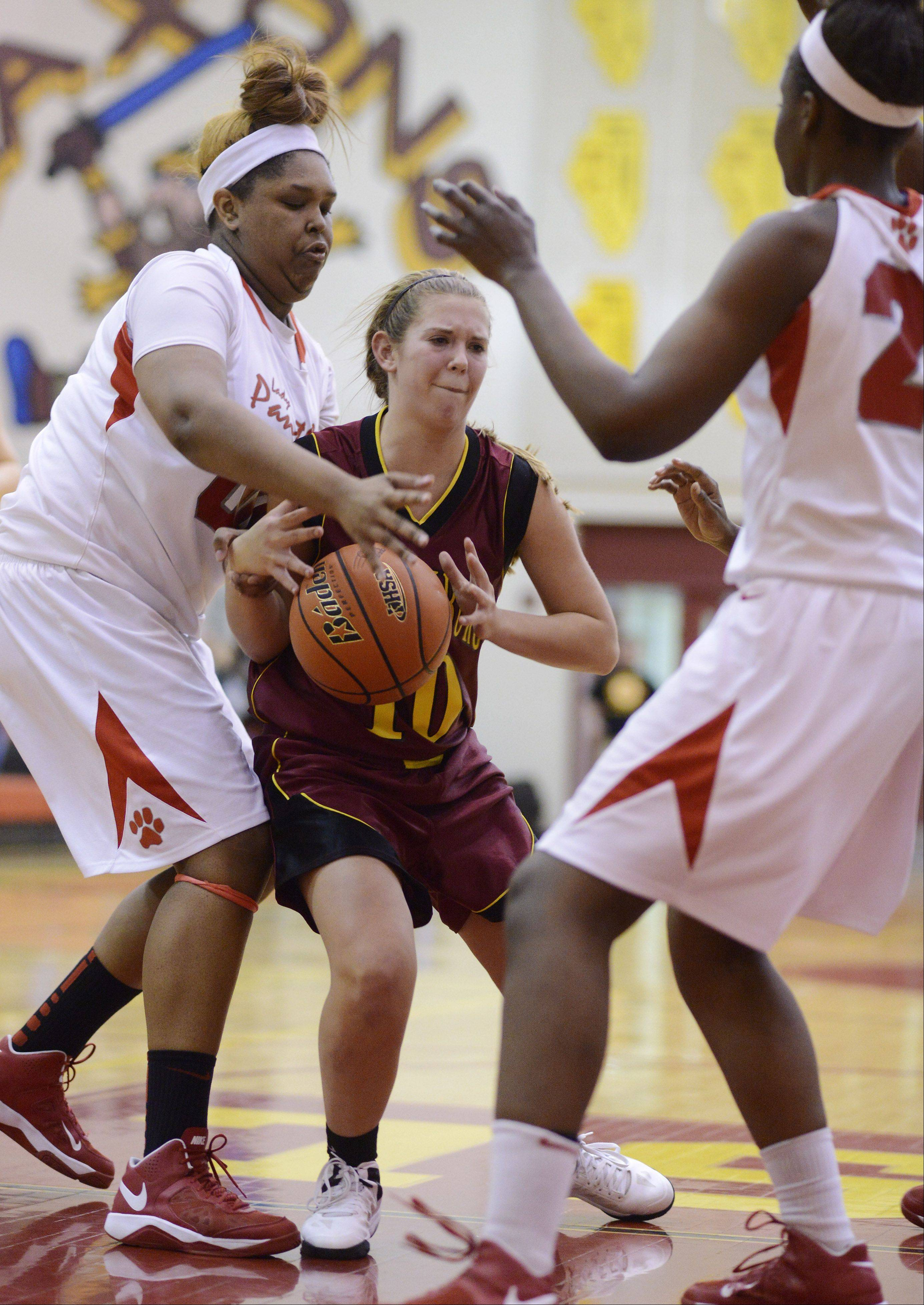 Schaumburg's Riley Williams, middle, tries to hang onto the ball after Proviso West defenders Taylor Pate, left, and Jade Wright fill the lane during Tuesday's Class 4A regional semifinal at Schaumburg.