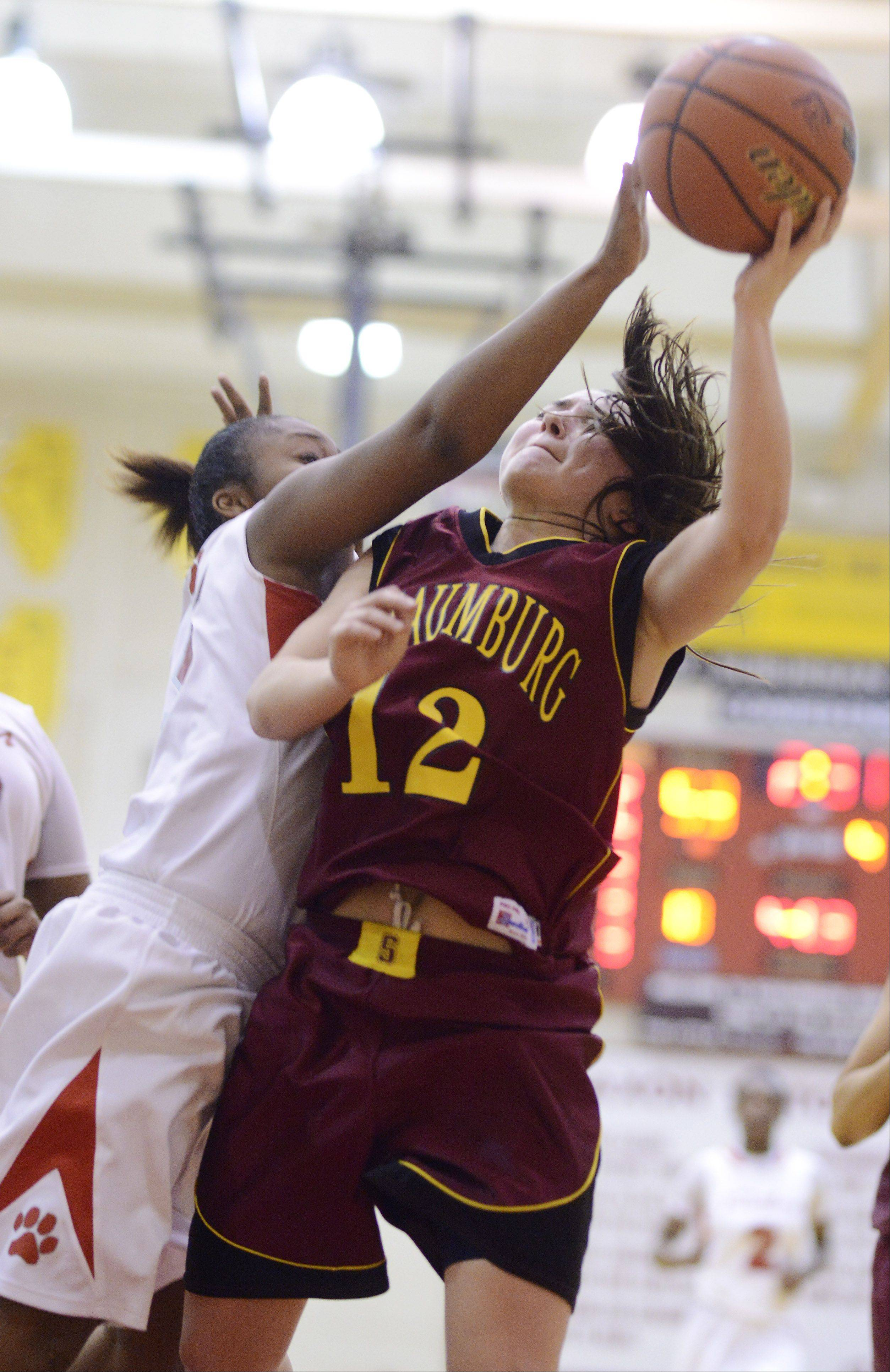 Schaumburg's Amanda Kelly, right, gets fouled on her way to the basket by Proviso West's Nia Roscoe during Tuesday's Class 4A regional semifinal at Schaumburg.