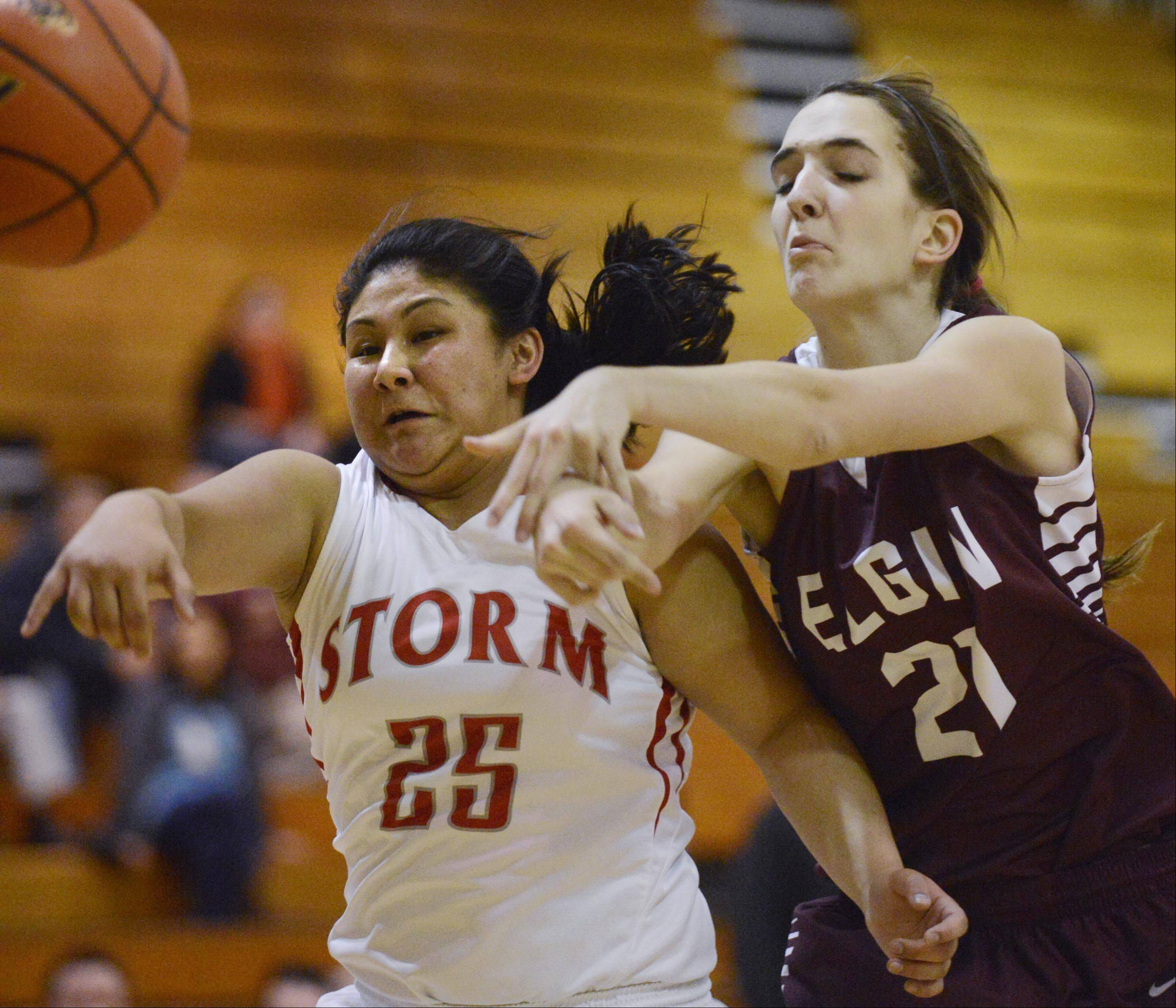 Elgin's Tamara Milosevic and South Elgin's Nadia Yang reach for the ball in Tuesday's Class 4A regional semifinal game in Streamwood.