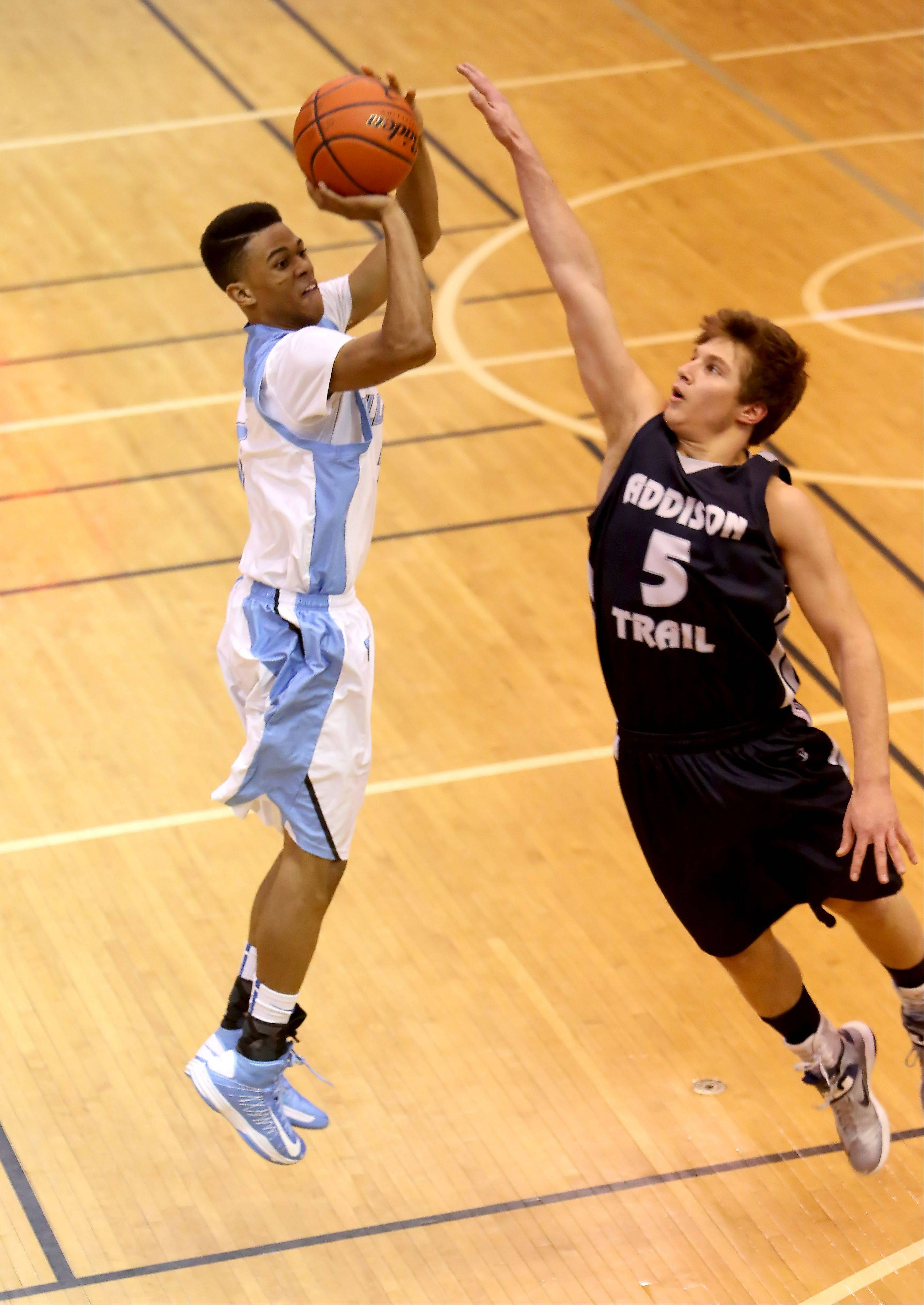Joshua Joiner, left, of Willowbrook goes up to shoot as James Pupillo, right, of Addison Trail goes up to block.