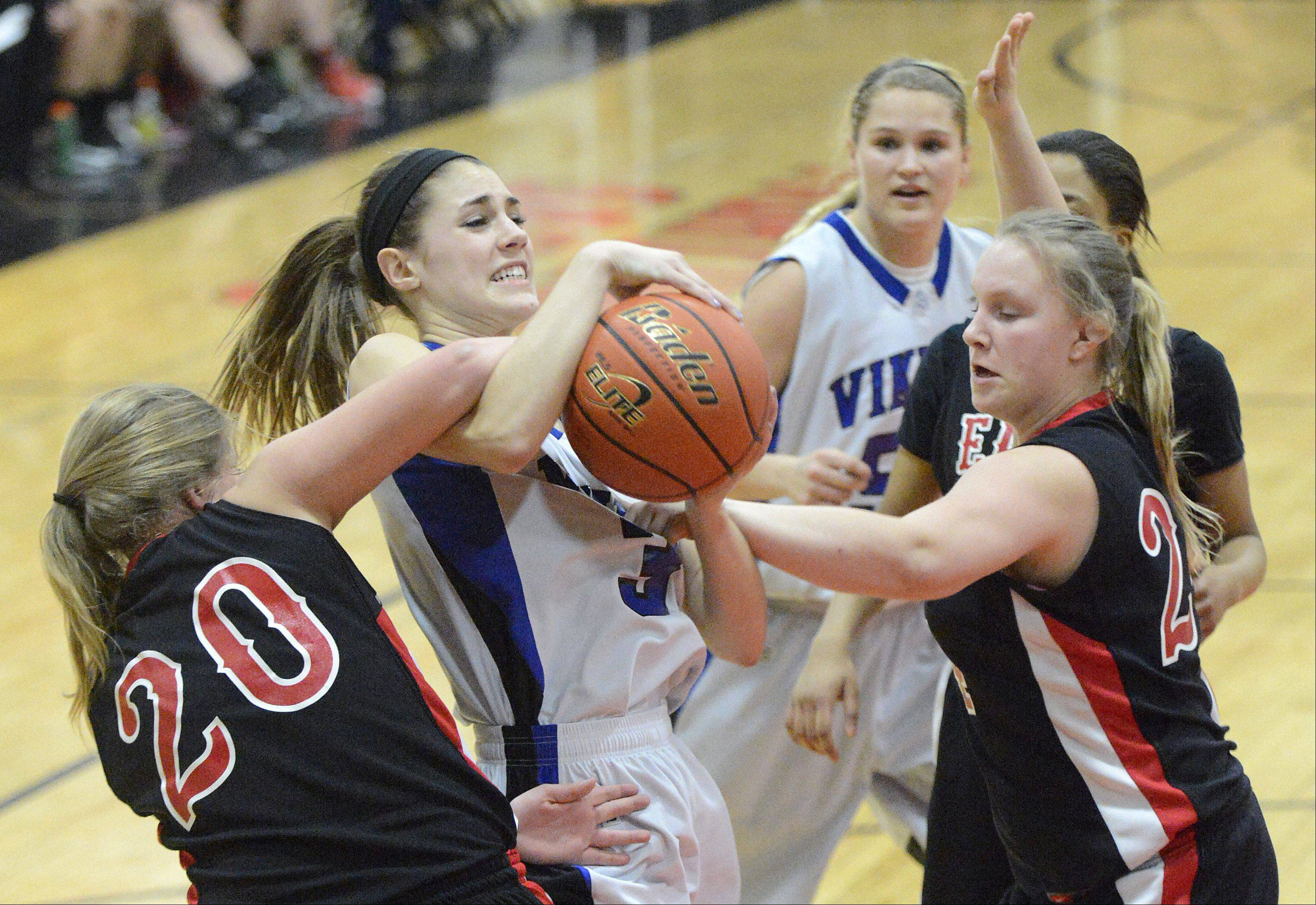 Glenbard East's Kara Tadda and Rachael Leifheit wrestle with Geneva's Madeline Dunn for a loose rebound in the third quarter.
