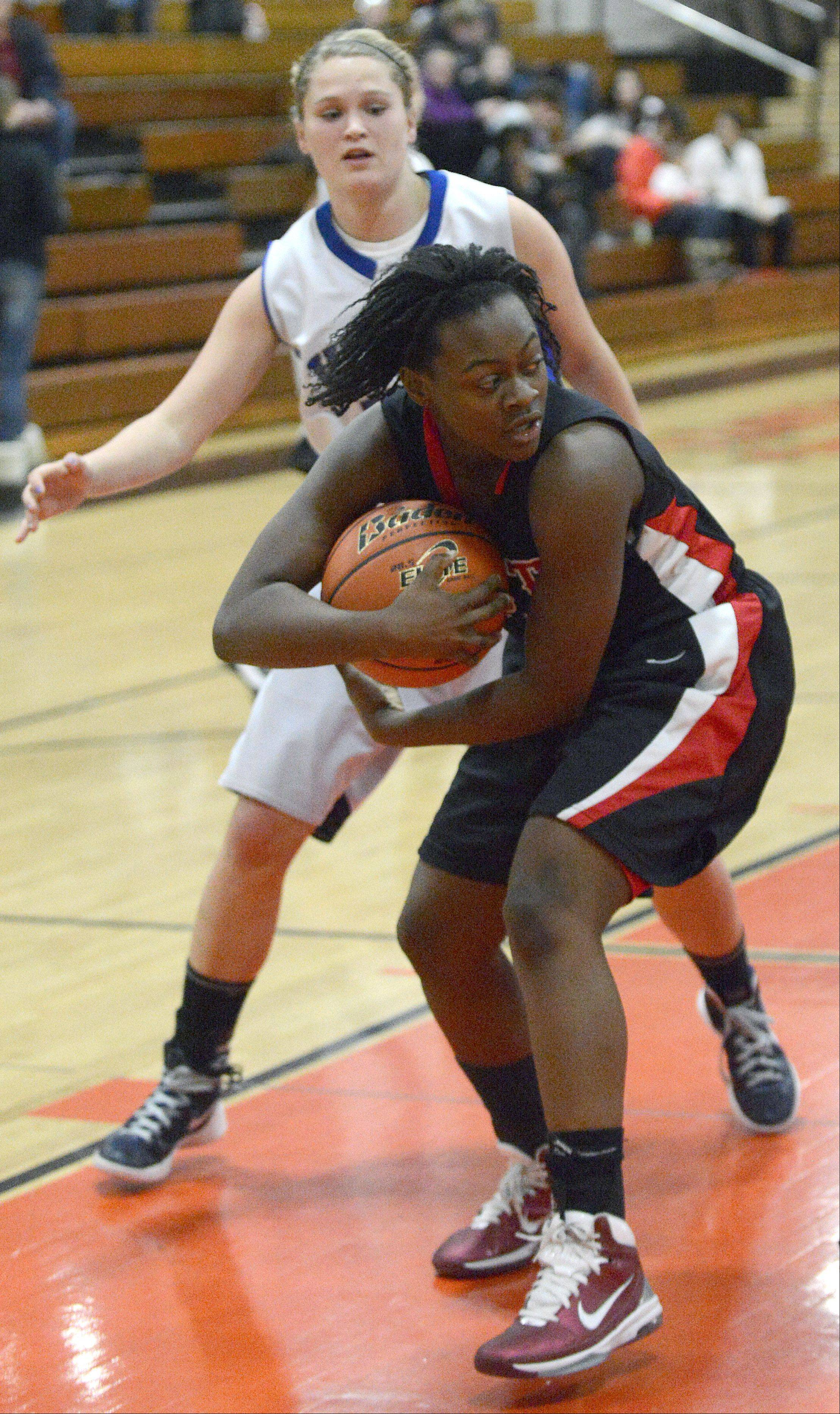 Glenbard East's Tajanae Key protects her rebound from Geneva's Janie McCloughan in the second quarter.