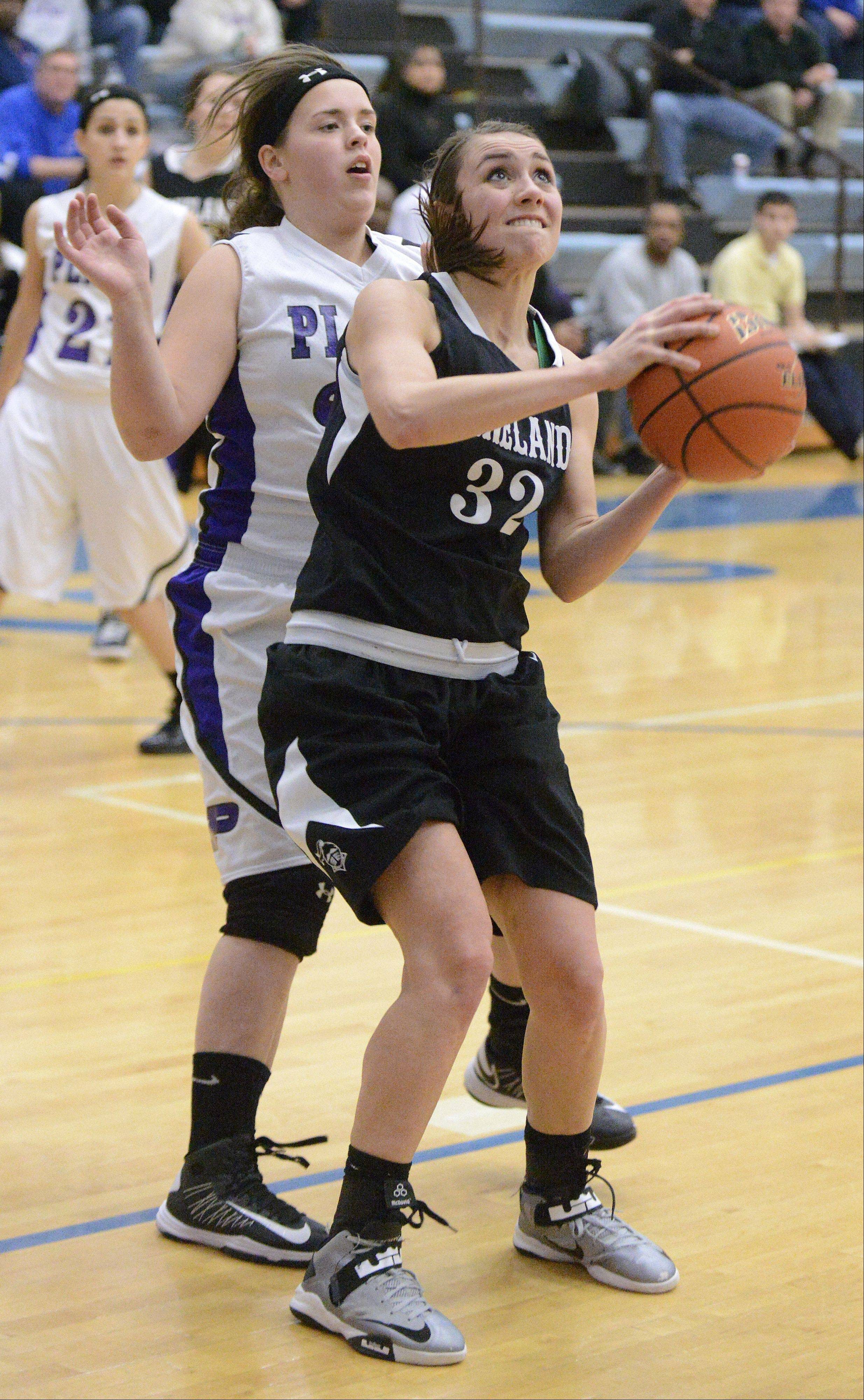 Kaneland's Emma Bradford attempts a shot after shaking off a block by Plano's Lauren Chernick in the third quarter of the Class 3A regional game on Wednesday, February 13.