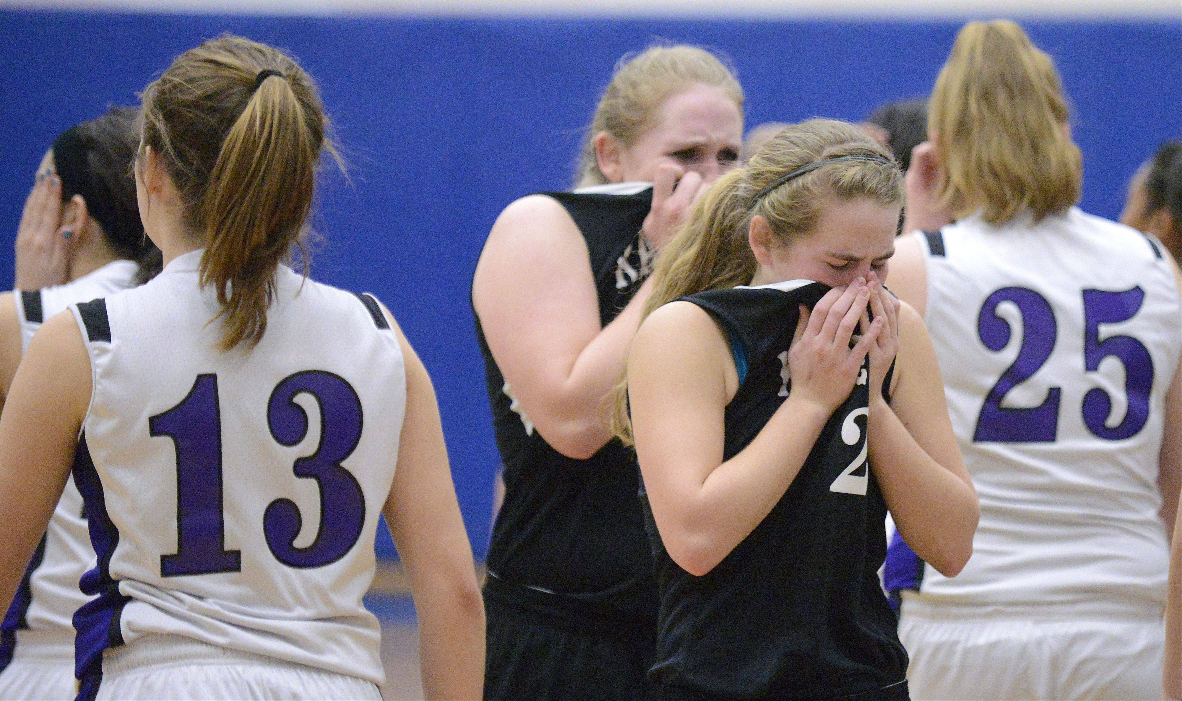 Kaneland's Sarah Grams and Ashley Prost walk through Plano players after their loss in the Class 3A regional game on Wednesday, February 13.