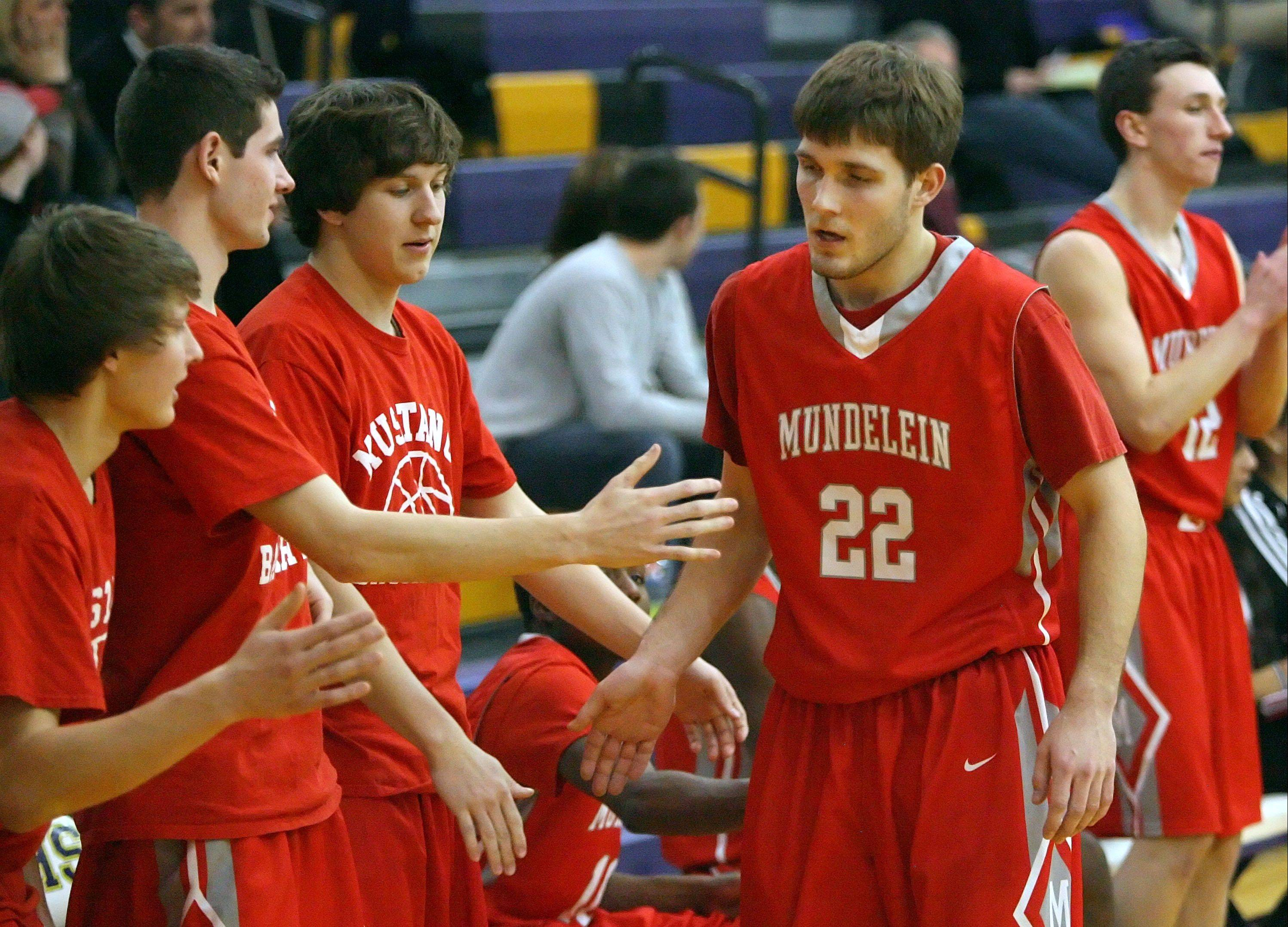 Mundelein's Robert Knar gets high-fives from the bench after breaking the all-time Mundelein scoring record held by Kyle Kessel on Wednesday night at Wauconda.