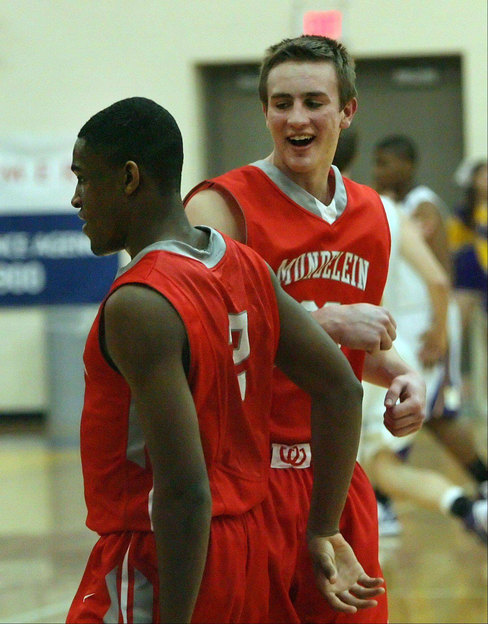 Mundelein's Sean O'Brien, right, celebrates with Chino Ebube after an alley-oop dunk Wednesday at Wauconda.