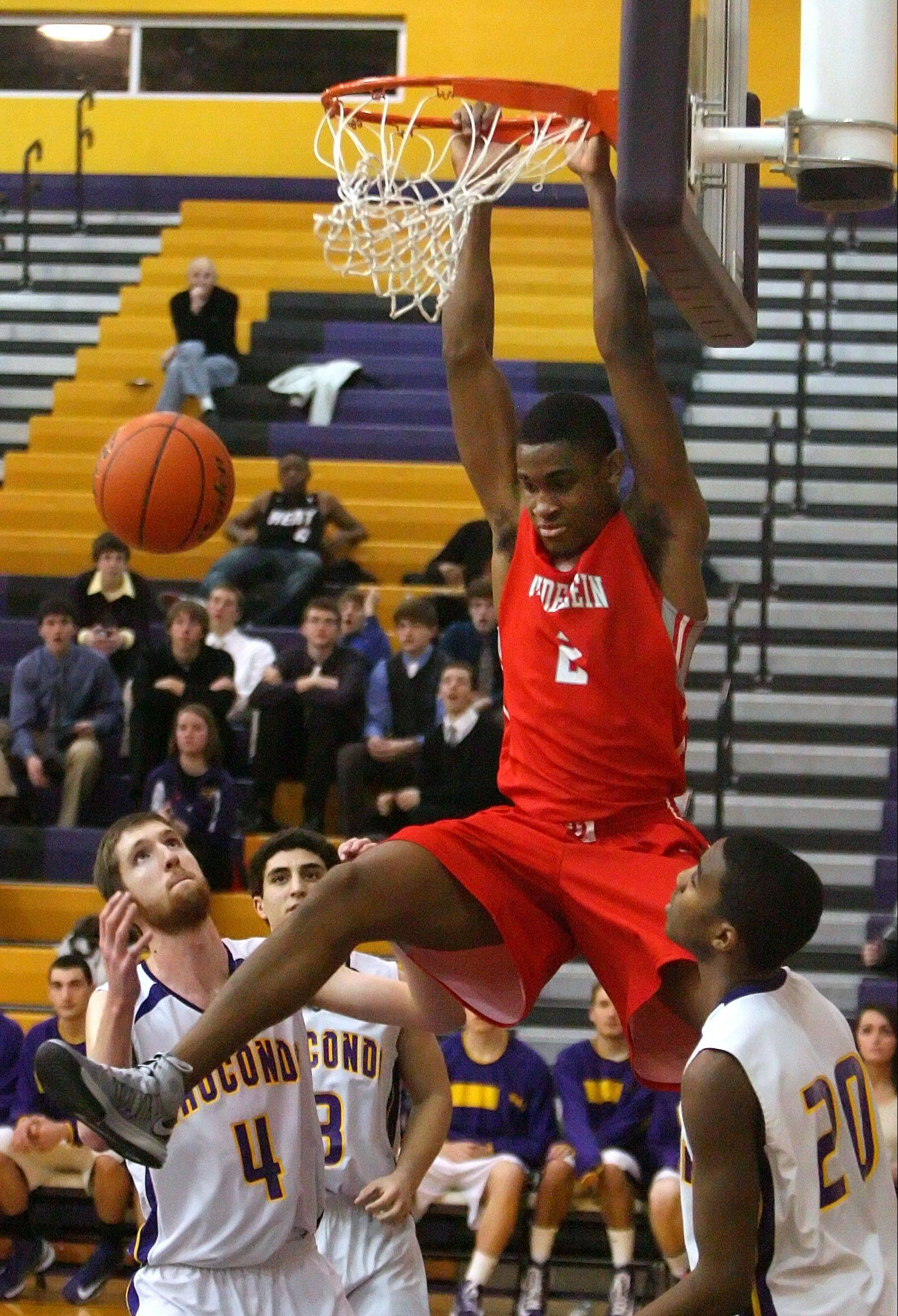 Mundelein's Chino Ebube goes in for an alley-oop dunk over Wauconda's Ricky Sidlowski, left, and Devon King on Wednesday night at Wauconda.