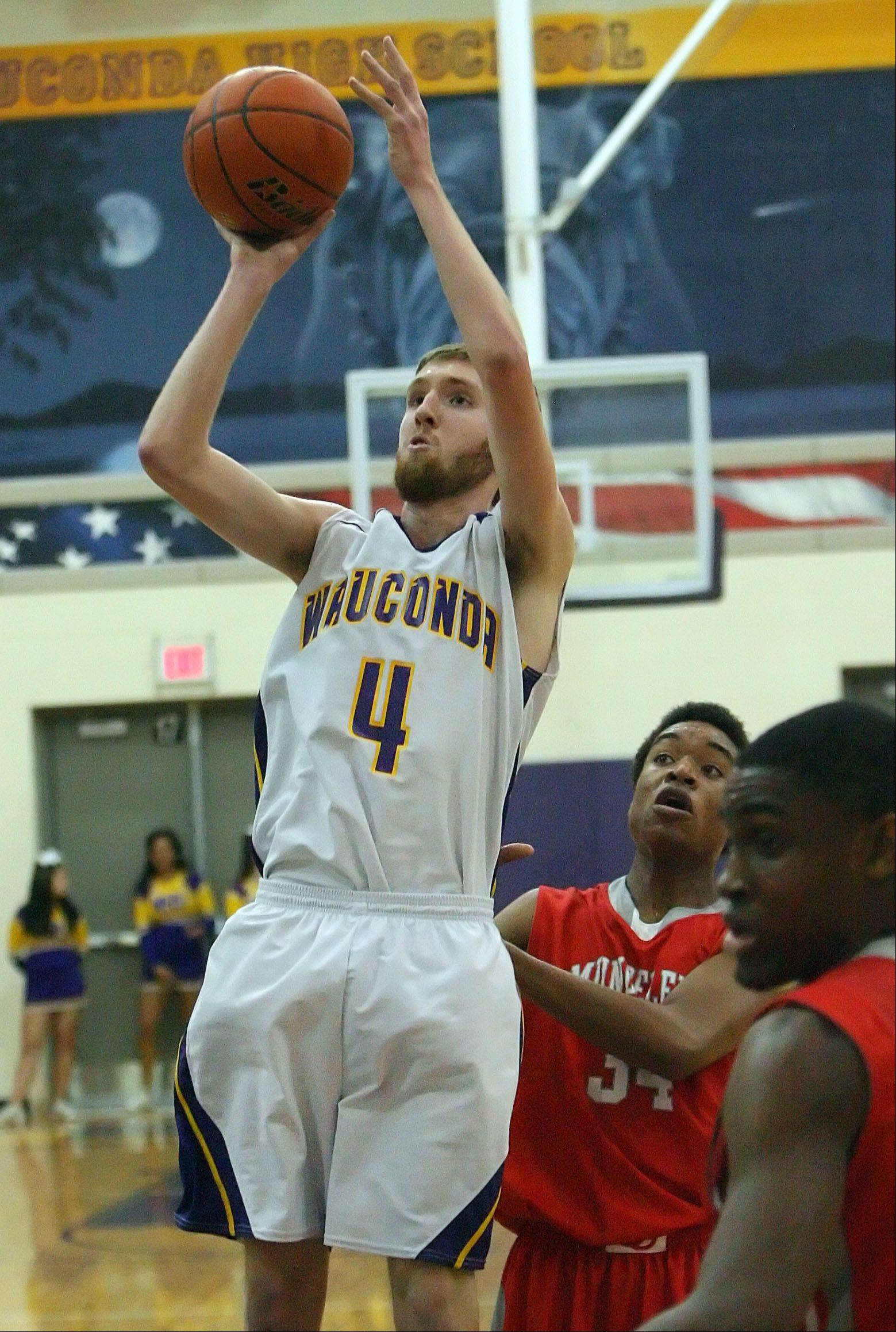 Wauconda's Ricky Sidlowski, left, shoots over Mundelein's Cliff Dunigan and Chino Ebube on Wednesday night at Wauconda.