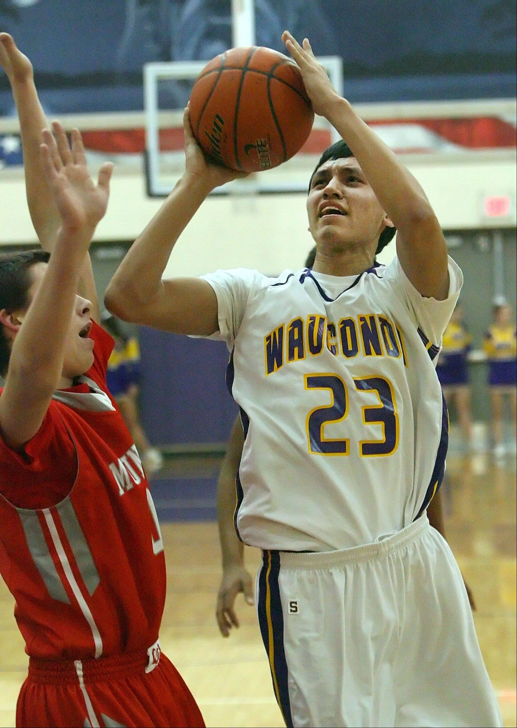 Wauconda's Kodey Thomas, right, drives on Mundelein's Derek Parola on Wednesday night at Wauconda.