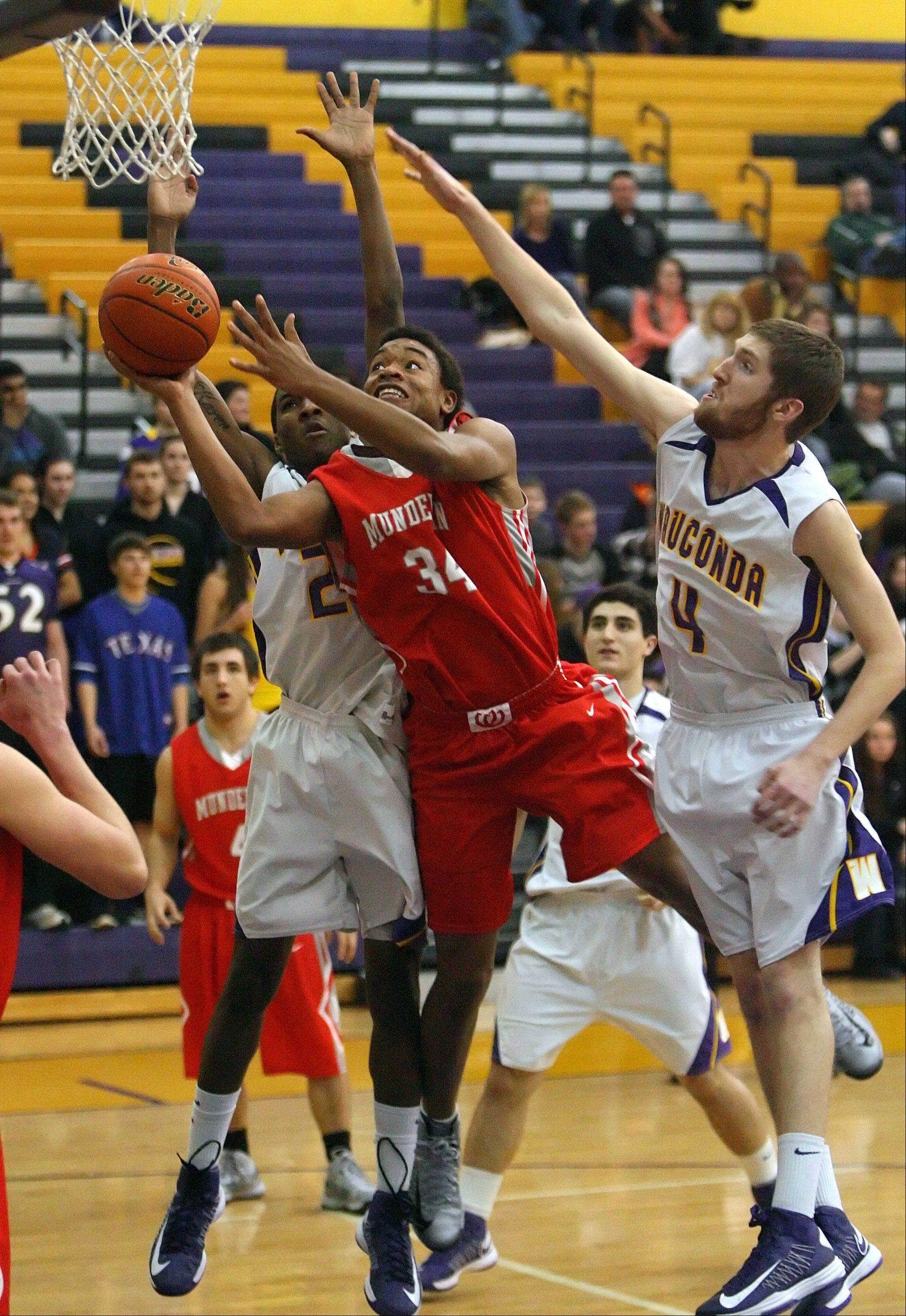 Mundelein's Cliff Dunigan drives past Wauconda's Devon King, left, and Ricky Sidlowski on Wednesday night at Wauconda.