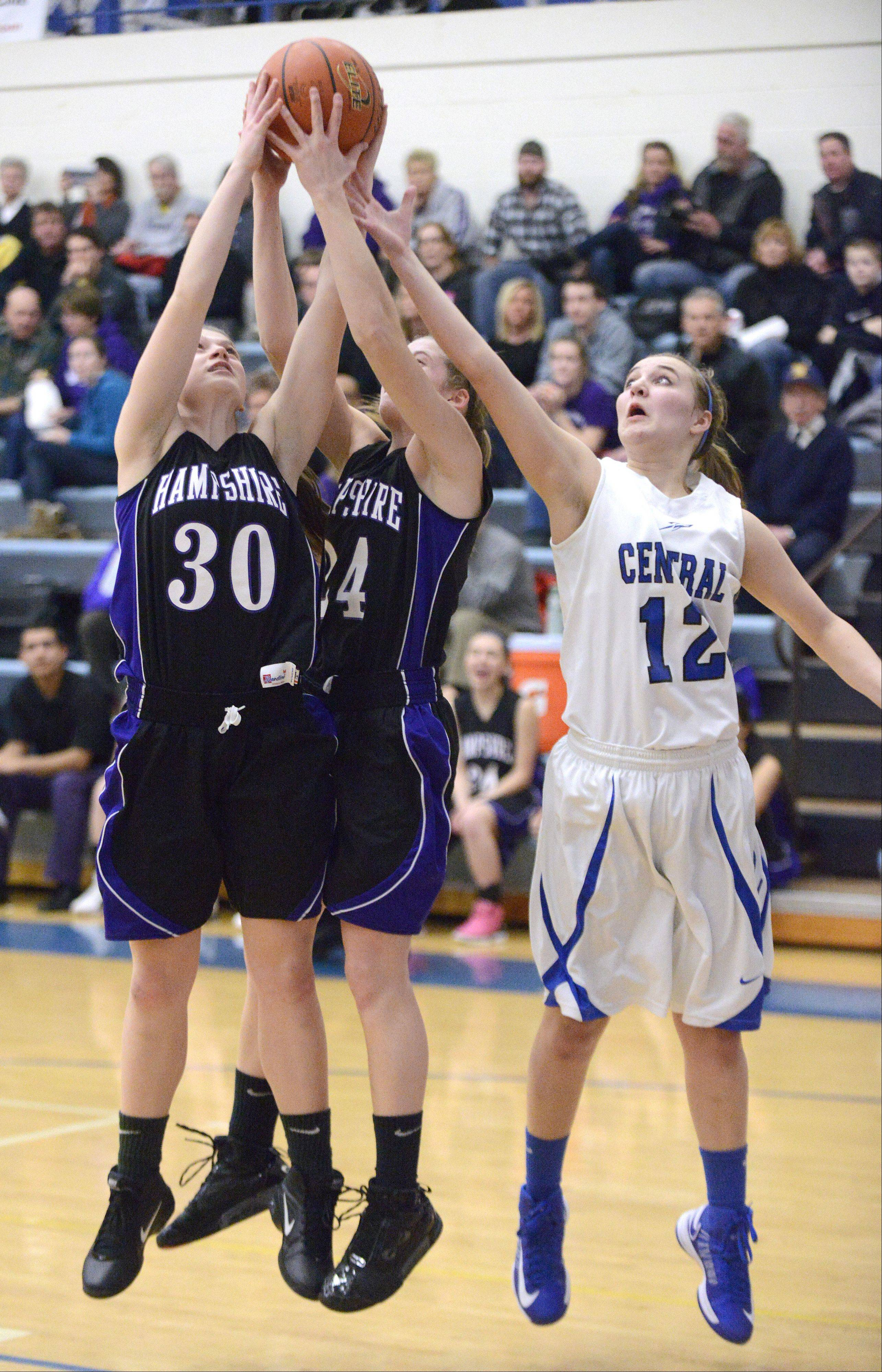 Hampshire's Tricia Dumoulin and Nikki Dumoulin reach for a rebound with Burlington Central's Shelby Holt in the second quarter.