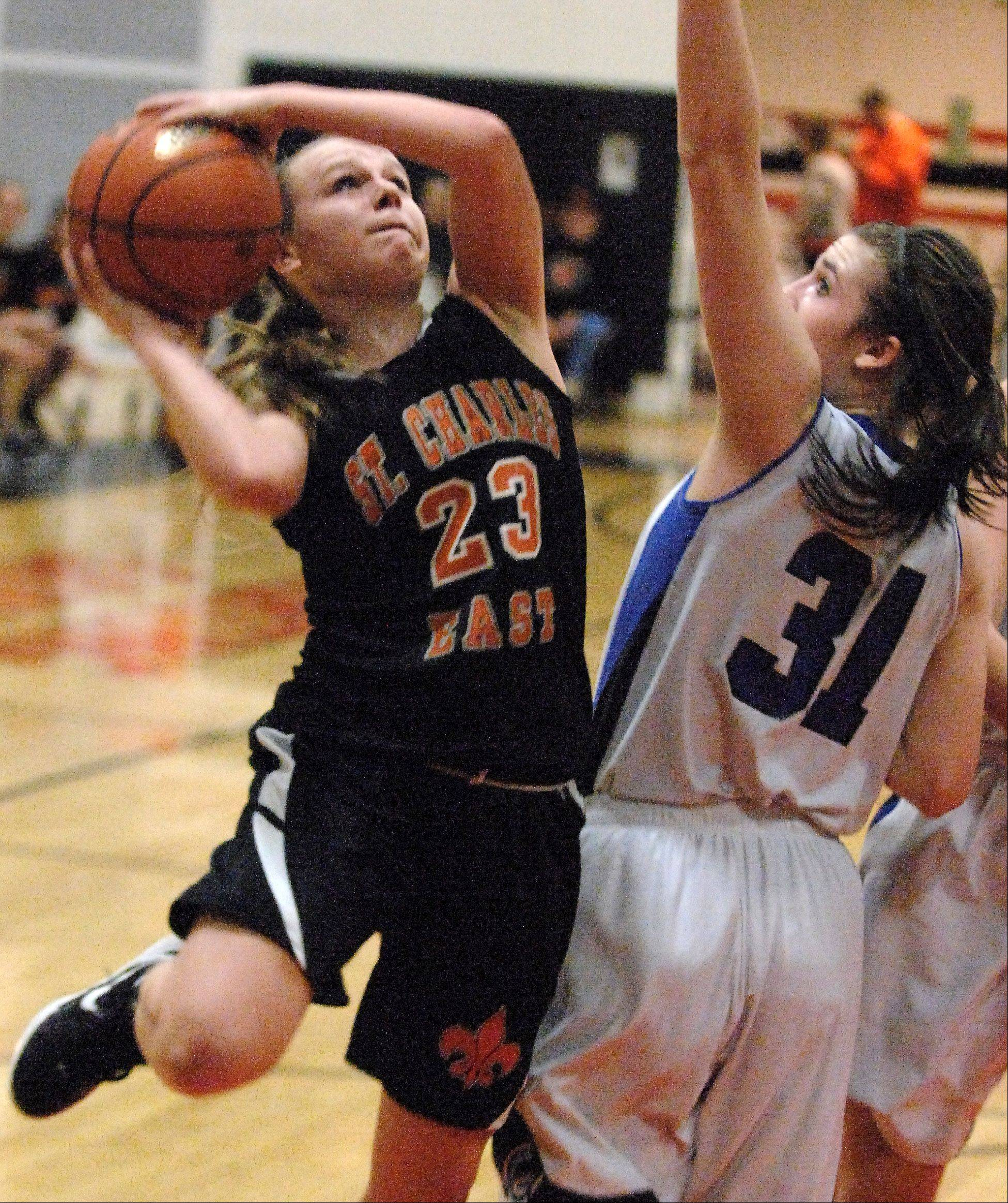 St. Charles East's Amanda Hilton puts up a shot over Geneva's Sami Pawlak during Thursday's regional championship game in St. Charles.