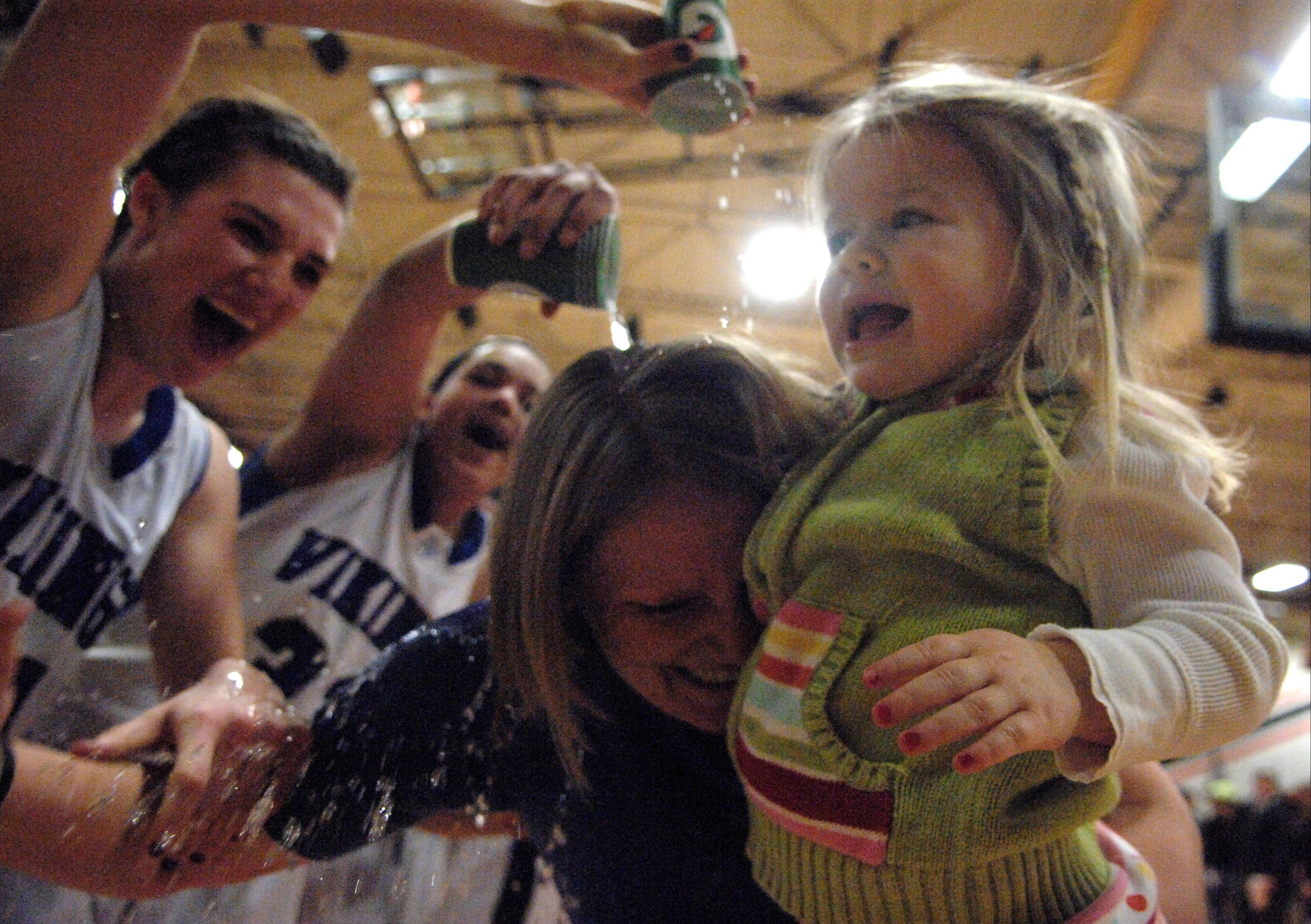 Geneva coach Sarah Meadows holds her niece Tess Kissack, 2, while her teams dumps cups of water on her following their win.