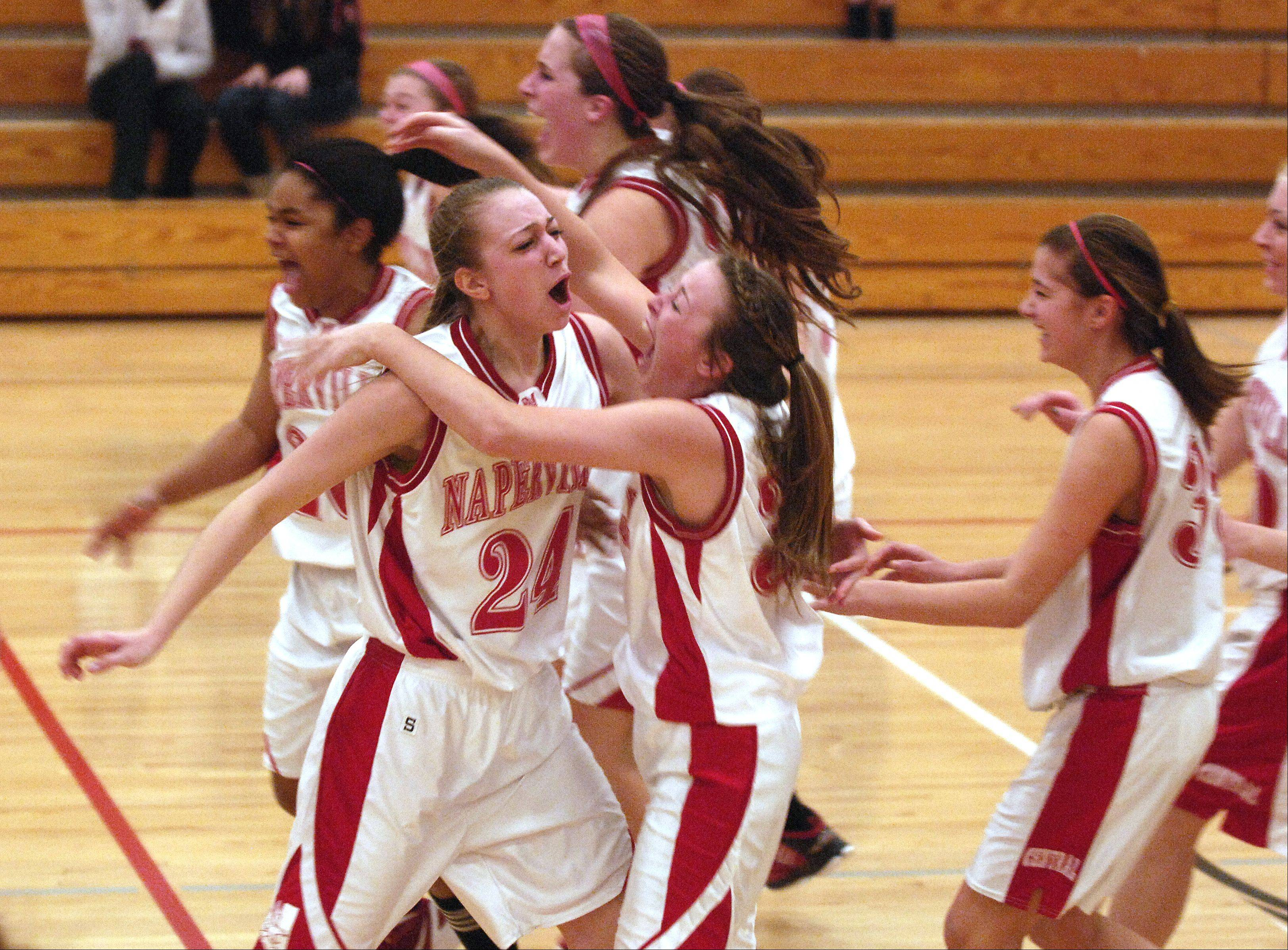 Naperville Central celebrates their wins of the girls Class 4A regional final basketball game over Benet Academy 44-42, Thursday in Lisle.